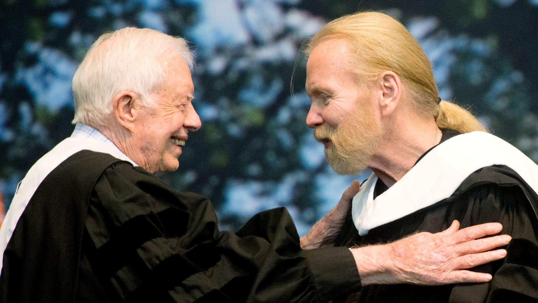 Jimmy Carter hugs Gregg Allman who received an honorary degree at Mercer University in Macon, Ga.