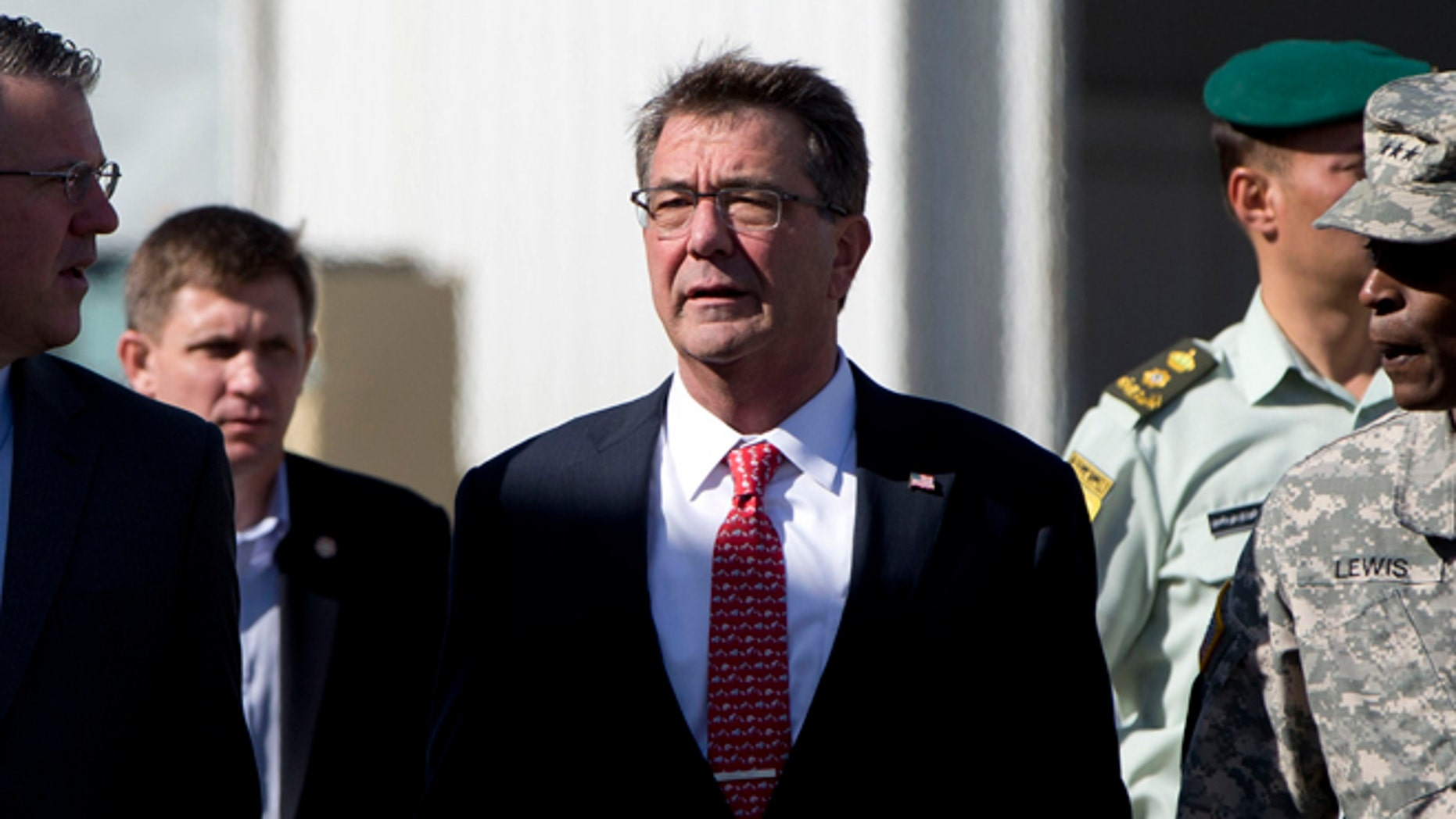 July 23, 2015: U.S. Defense Secretary Ash Carter, joined by U.S. Army Lt. Gen. Ron Lewis, right, and Chief of Staff Eric Rosenbach, left, walks the tarmac before boarding his plane at Queen Alia Airport in Amman, Jordan, en route to Baghdad, Iraq.