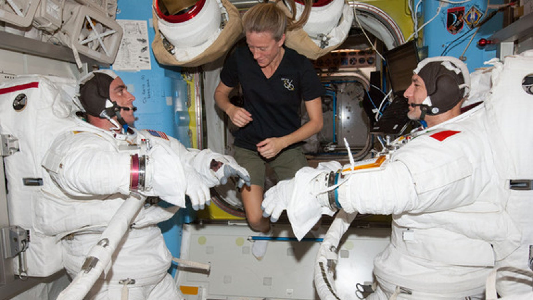 """Flight Engineers Chris Cassidy (left) and Luca Parmitano participate in a """"dry run"""" in the International Space Station's Quest airlock in preparation for the first of two spacewalks in July 2013. Flight Engineer Karen Nyberg (center) assists."""