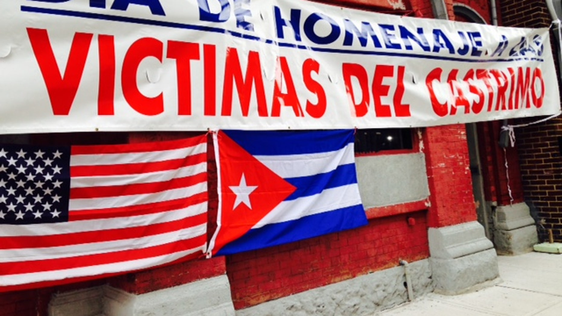"Banner outside Union City headquarters of Former Cuban Political Prisoners says: ""Day of Homage to Castro's Victims."""
