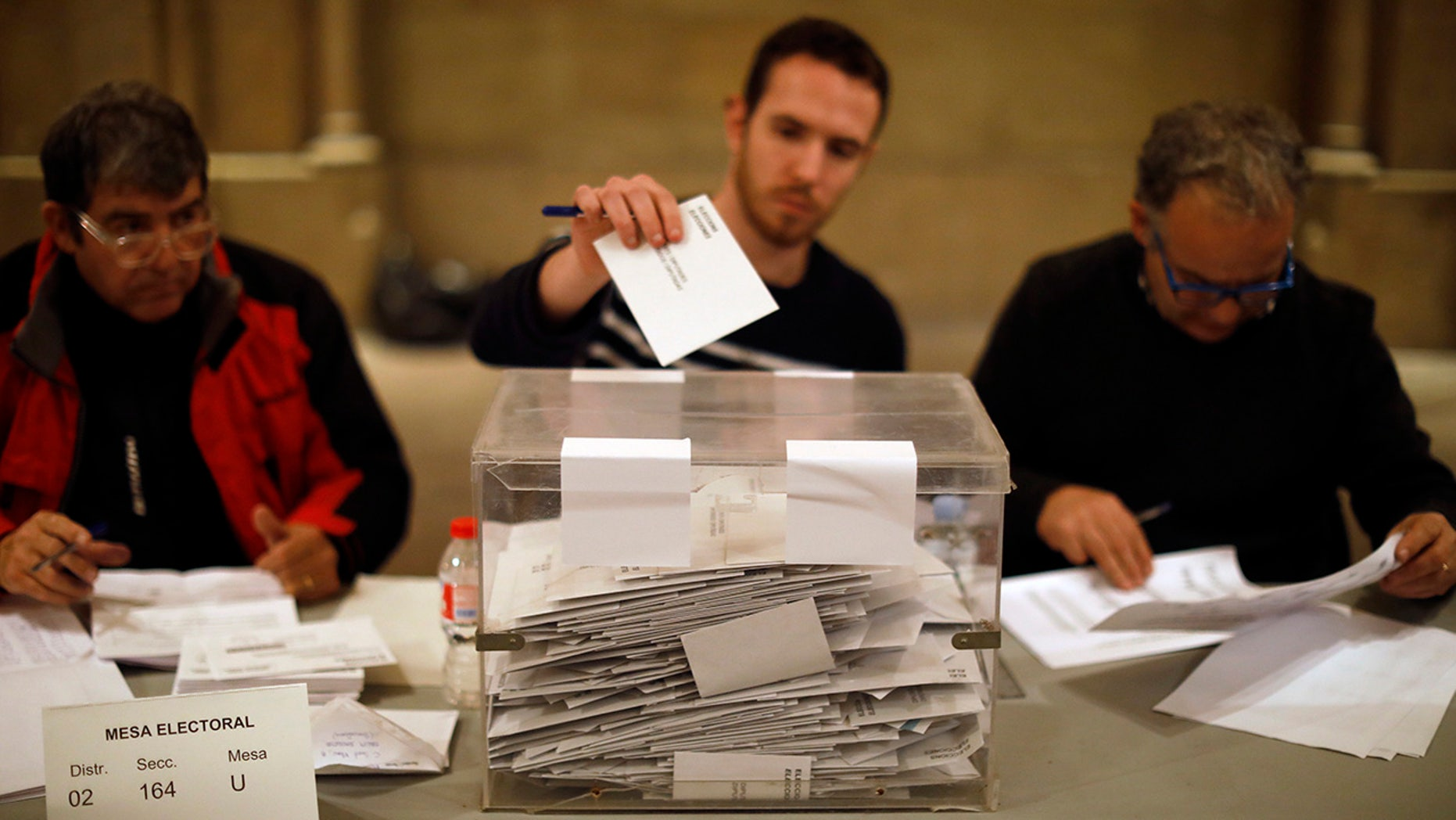 As polls close, election workers cast their own ballots for the Catalan regional election in a polling station at the Barcelona University in Barcelona, Spain, on Thursday, Dec. 21, 2017.