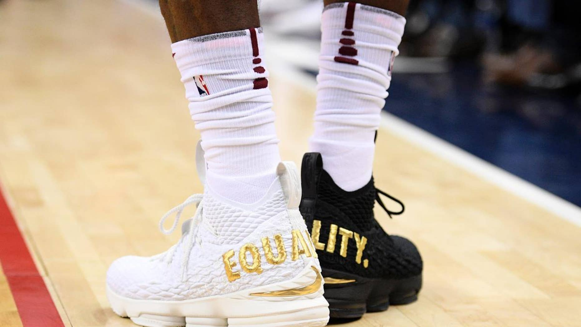"LeBron James made a statement during an NBA game with his shoes — one black, one white, with the word ""equality"" in capital gold letters on the back of each."