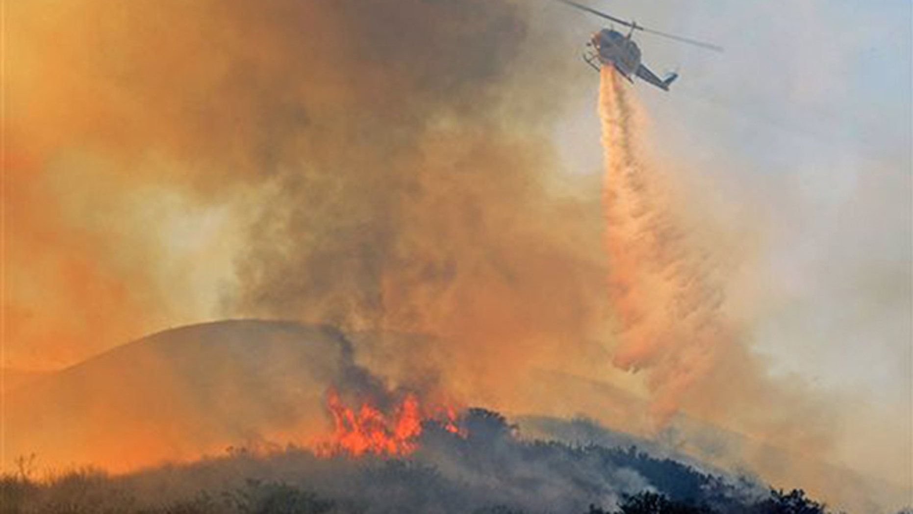 A Ventura County Fire helicopter makes a water drop on an oil field service road while working a wildfire in Ventura County, Calif. on Saturday, Dec. 26, 2015. (Mike Eliason/Santa Barbara County Fire Dept. via AP)
