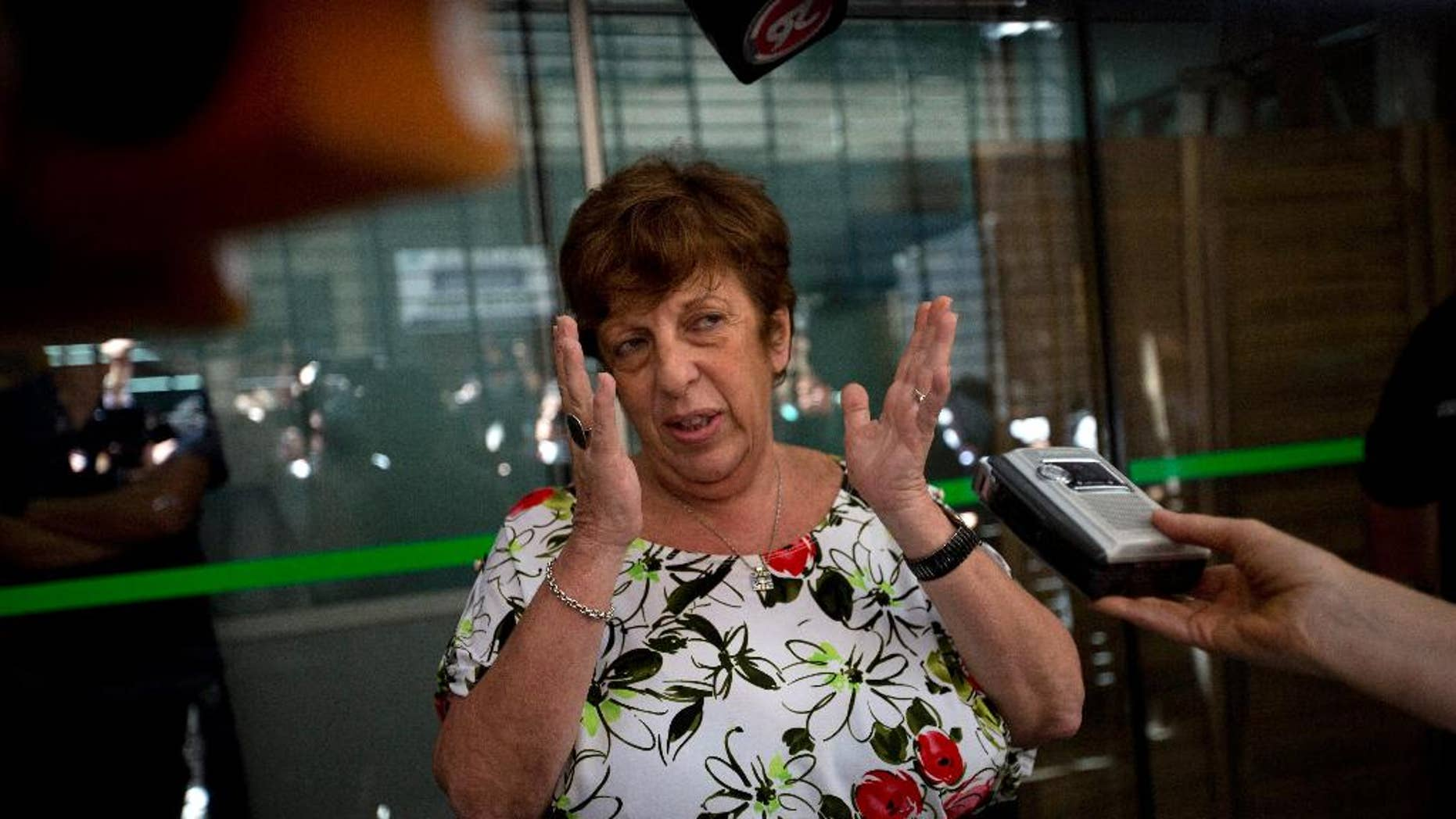 FILE - In this  Jan. 22, 2015, file photo, Viviana Fein, who leads the investigation of prosecutor Alberto Nisman's death, speaks with reporters outside her office, in Buenos Aires, Argentina. Fein the lead investigator in the mysterious death of Nisman who had accused Argentina's president of wrongdoing came under sharp criticism Monday, June 1, 2015, for a video showing police working without latex gloves where Alberto Nisman's body was found. (AP Photo/Rodrigo Abd, File)