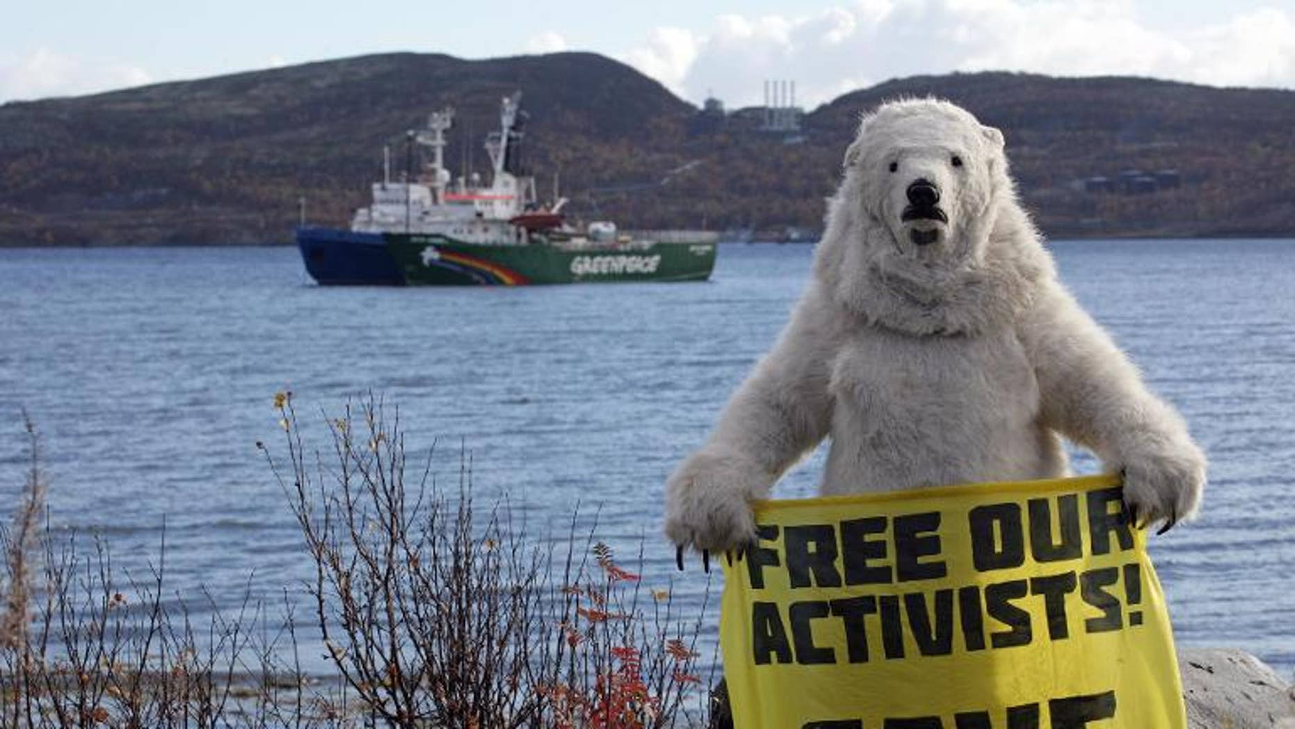 An activist dressed as a polar bear holds a banner in front of Greenpeace's Arctic protest ship, moored beside a Russian Coast Guard ship in Kola Bay near Murmansk on September 24, 2013, in a photo provided by Greenpeace International