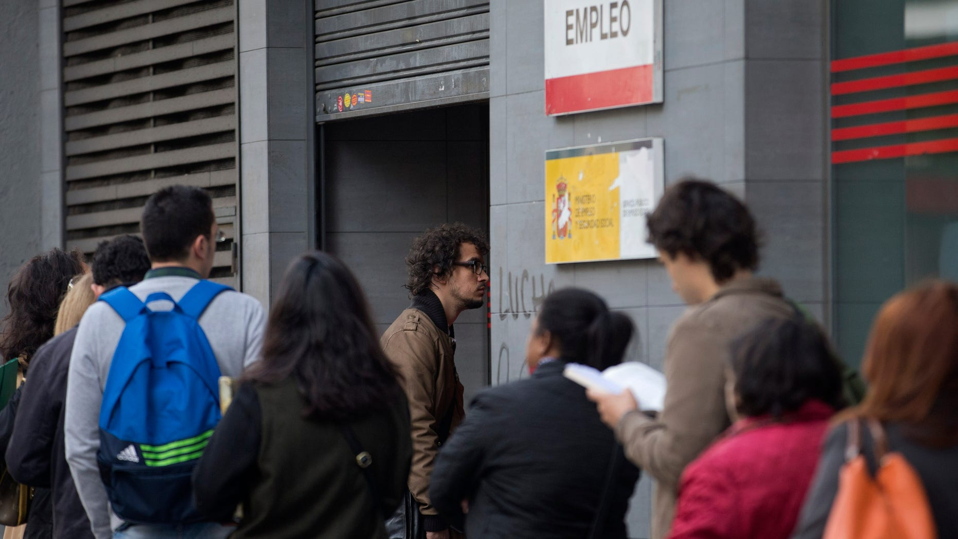 People queue to enter a government unemployment office in Madrid, Spain, Tuesday Oct. 5, 2013. The number of people registered as unemployed in Spain rose by a little over 87,000 in October as many jobs created in the summer tourist season come to an end. The increase comes amid some hopeful signs over Spain's economy with a two-year recession coming to an end in the third quarter, albeit with modest quarterly growth of 0.1 percent. (AP Photo/Paul White)