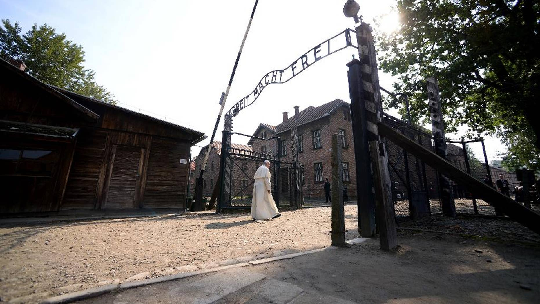 Pope Francis walks through the gate of the former Nazi German death camp of Auschwitz in Oswiecim, Poland, Friday, July 29, 2016.  Pope Francis paid a somber visit to the Nazi German death camp of Auschwitz-Birkenau Friday, becoming the third consecutive pontiff to make the pilgrimage to the place where Adolf Hitler's forces killed more than 1 million people, most of them Jews. (Filippo Monteforte/Pool Photo via AP)