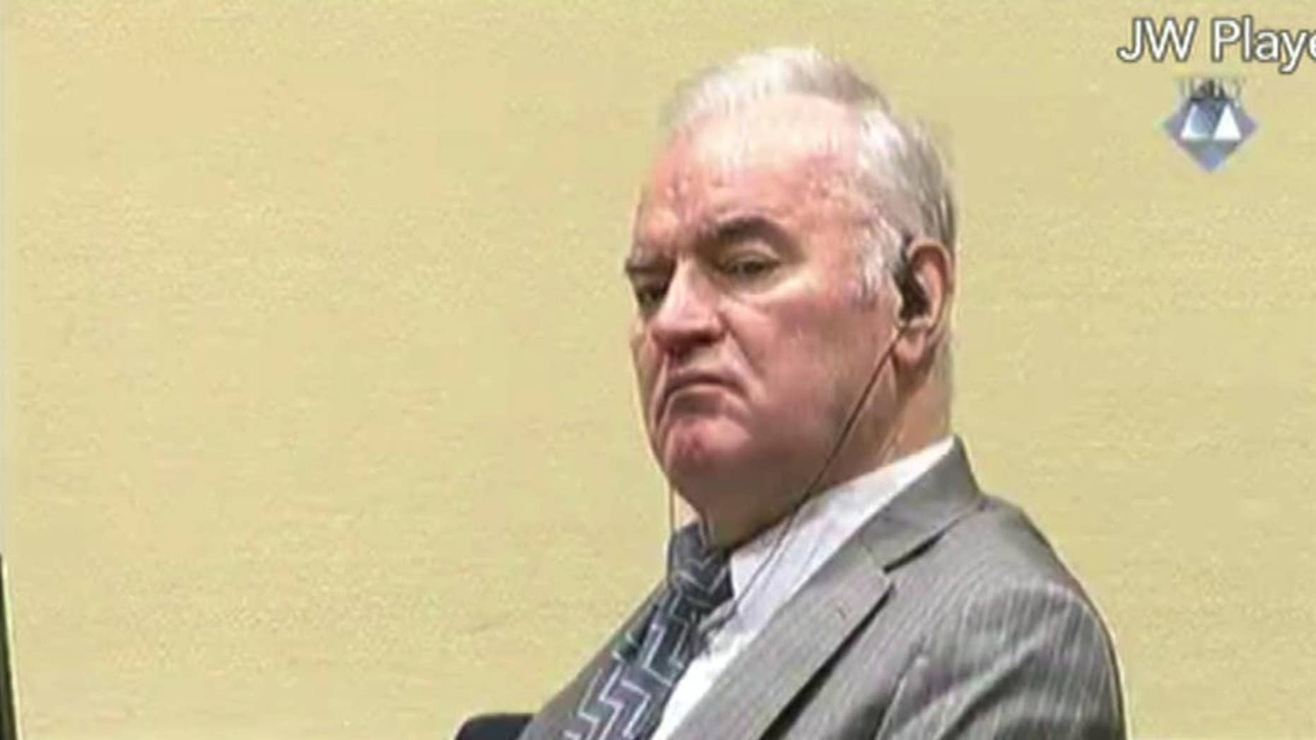 FILE - This is a Monday Dec. 5, 2016 file photo of Former Bosnian Serb military chief General Ratko Mladic looks across the court room at the International Criminal Tribunal for the Former Yugoslavia in the Hague Netherlands in this image taken from video. Gen. Ratko Mladic's defense team called on United Nations judges Tuesday Dec. 13, 2016  to acquit the former Bosnian Serb military chief, arguing that prosecutors failed to prove he orchestrated atrocities by Serb forces under his command during the Bosnian War.   (ICTY Video, File via AP)