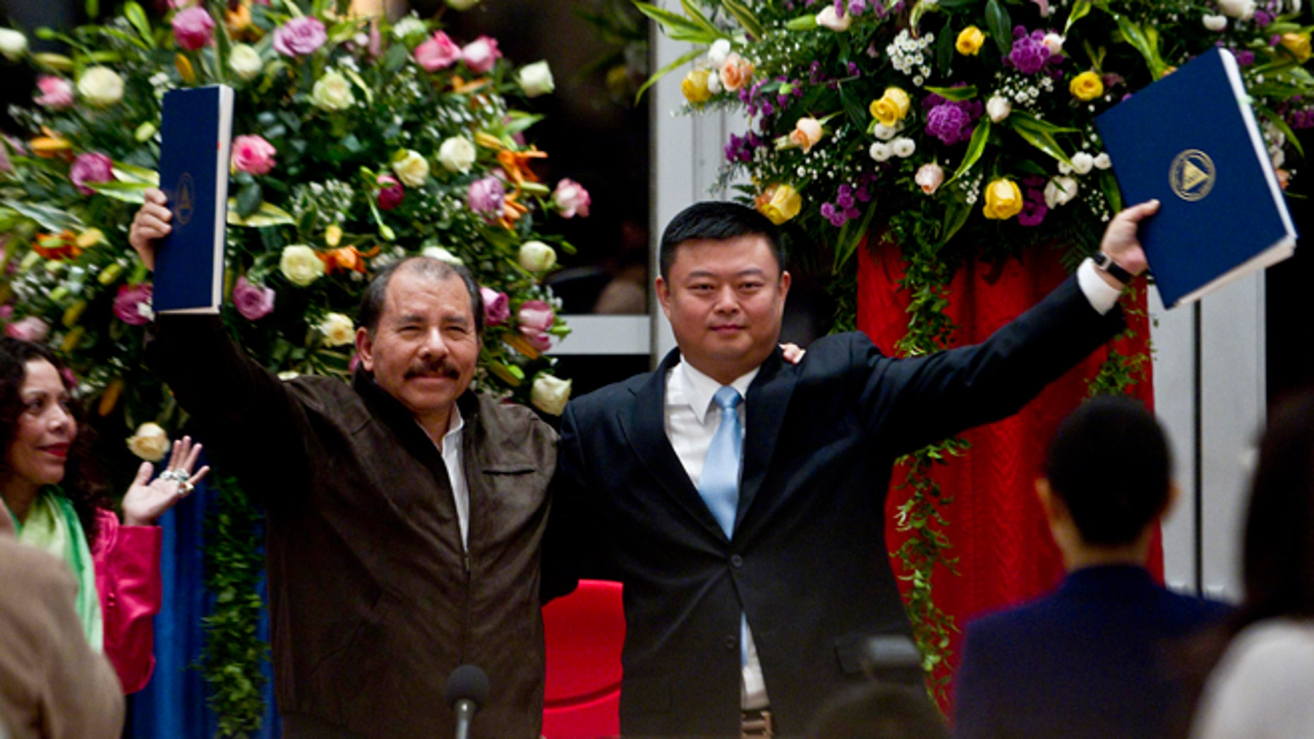 FILE - In this June 14, 2013 file photo, President Daniel Ortega, left, and Chinese businessman Wang Jing hold up a concession agreement for the construction of a multibillion-dollar canal at the Casa de los Pueblos in Managua. Nicaraguas government and Chinas HKND Group on Monday July 7, 2014, unveiled the route of a proposed inter-ocean canal to compete with the Panama Canal that Sandinista officials hope with lift the Central American country out of poverty. (AP Photo/Esteban Felix, File)