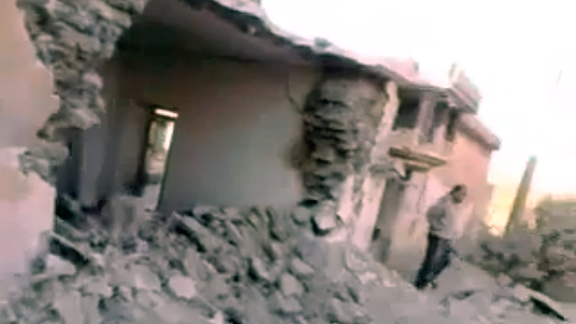 Sept. 22, 2012: In this image taken from video obtained from the Shaam News Network, SNN, which has been authenticated based on details in it, show damaged buildings and a bomb crater from government shelling  at Al-Bil village near the Turkish border, Idlib, Syria.