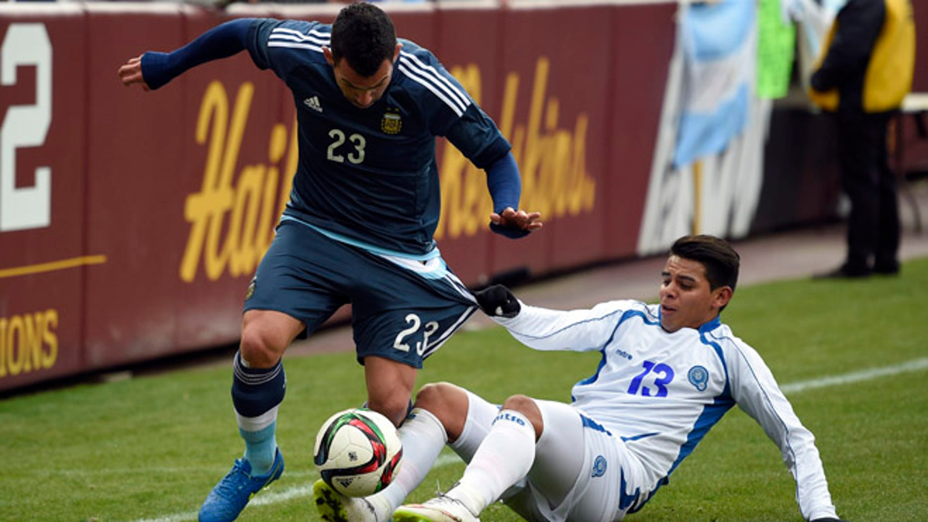 El Salvador's Alexander Larin (13) pulls on the shorts of Carlos Tevez (23) during the first half of an international friendly soccer game Saturday, March 28, 2015, in Landover, Md. (AP Photo/Nick Wass)