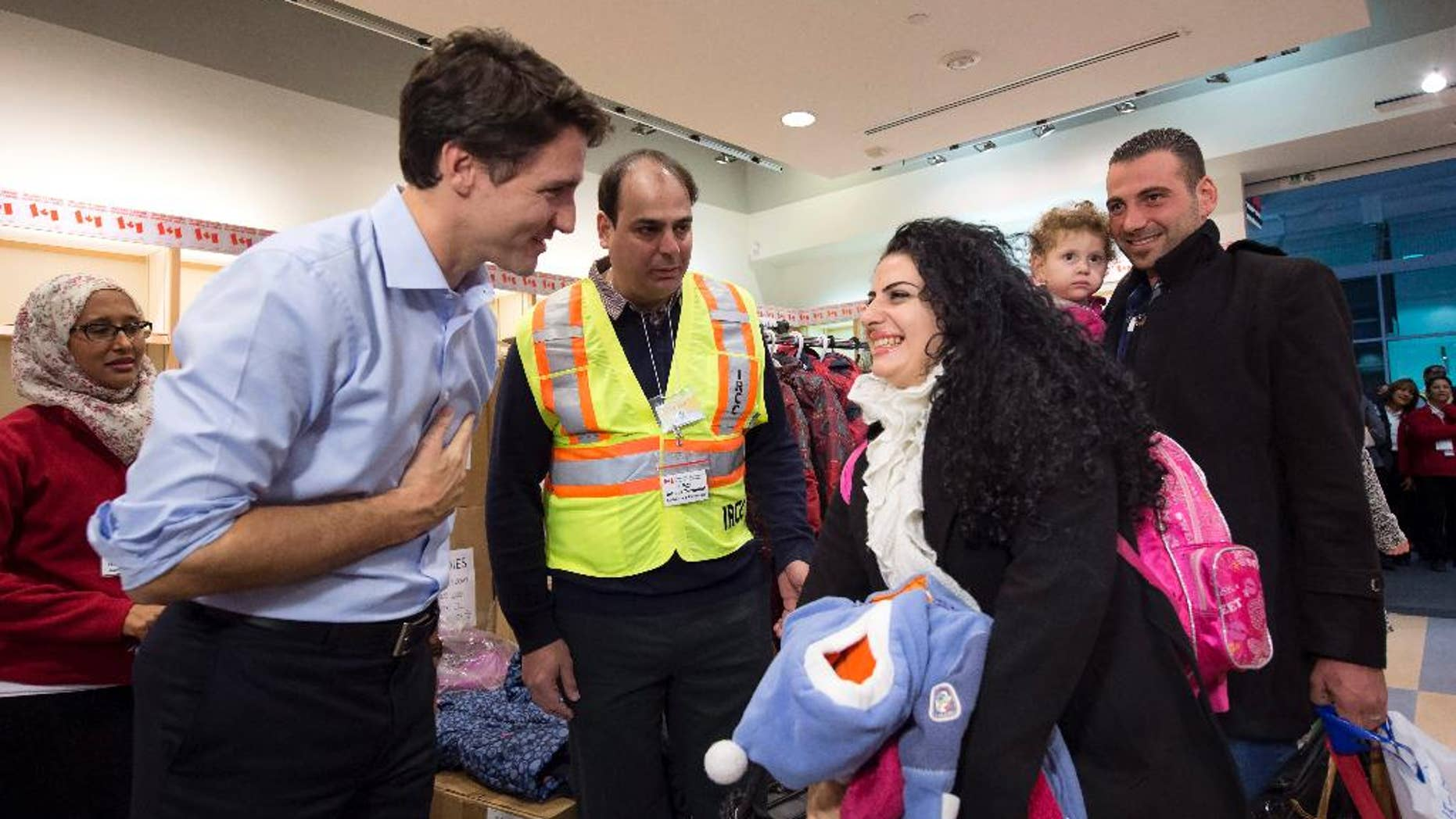 FILE - In this Dec. 11, 2015 file photo, Prime Minister Justin Trudeau, left, greets Georgina Zires, center, Madeleine Jamkossian, second right, and her father Kevork Jamkossian, refugees fleeing from Syria, as they arrive at Pearson International airport, in Toronto.