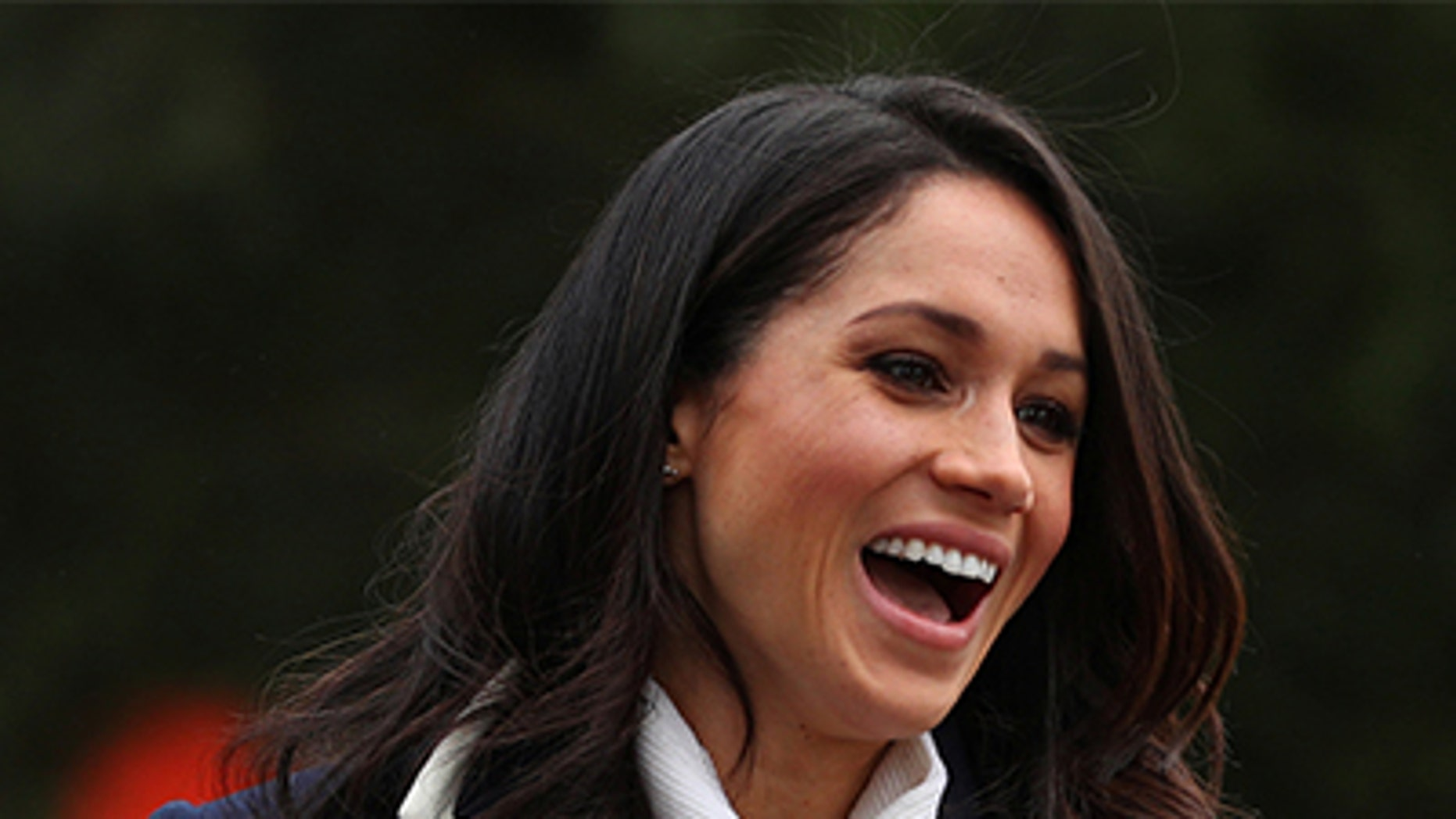 Meghan Markle layered her cozy wrap coat over a white All Saints turtleneck and black cigarette Alexander Wang pants.