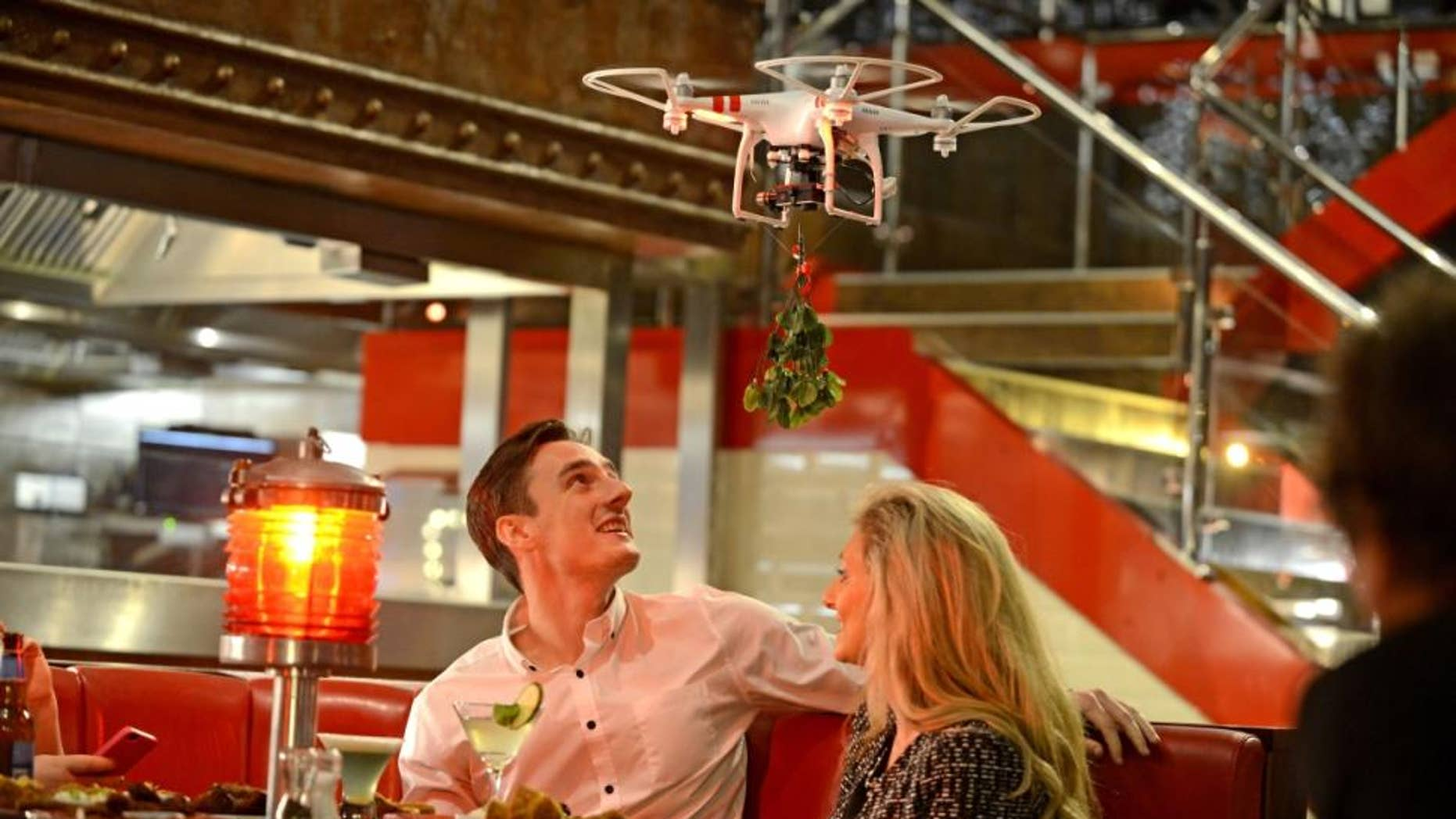 A Mobile Mistletoe drone hovers over a couple.