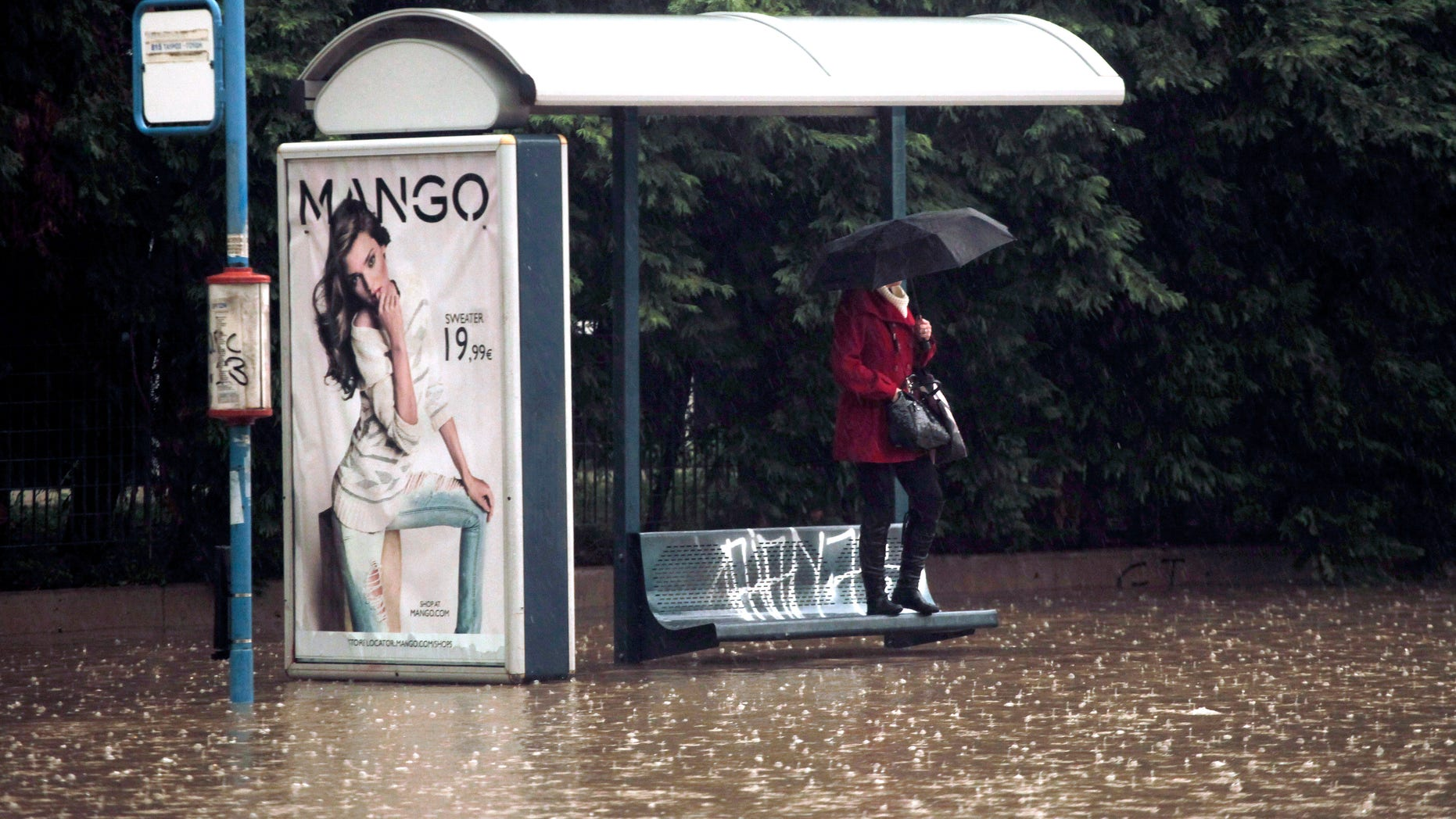 A woman shelters from the rain and the flodding at a bus stop, by standing on a bench, on a flooded highway linking Athens with its port of Piraeus, during a rainstorm on Friday, Feb. 22, 2013. Hours of heavy rainfall in Athens caused extensive flooding, inundating basements and forcing authorities to close major roads and a central subway station. The Greek fire brigade says it received more than 900 calls to pump out water in the greater Athens region Friday. (AP Photo/Petros Giannakouris)