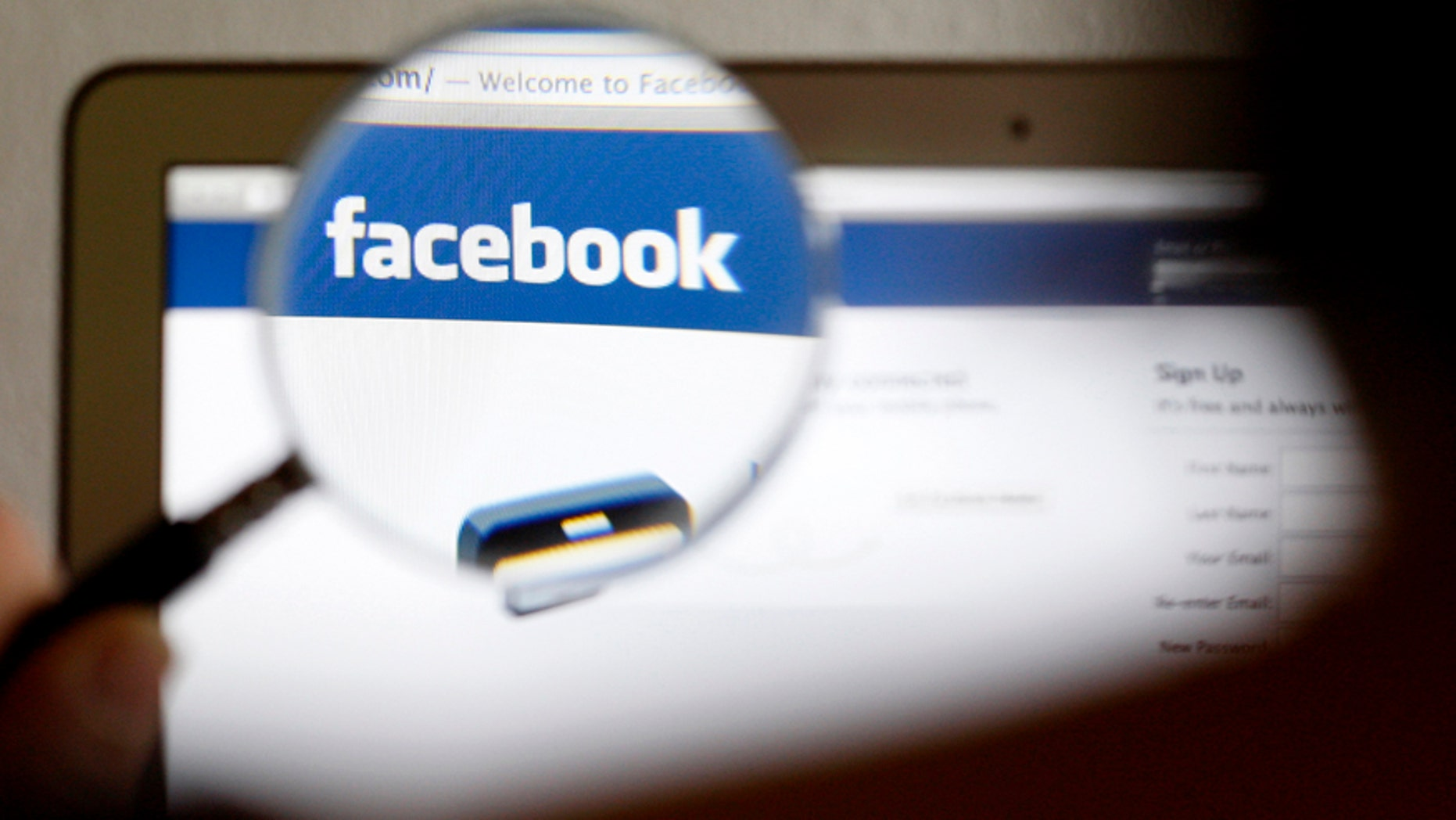 A Facebook logo on a computer screen is seen through a magnifying glass held by a woman in Bern, May 19, 2012.