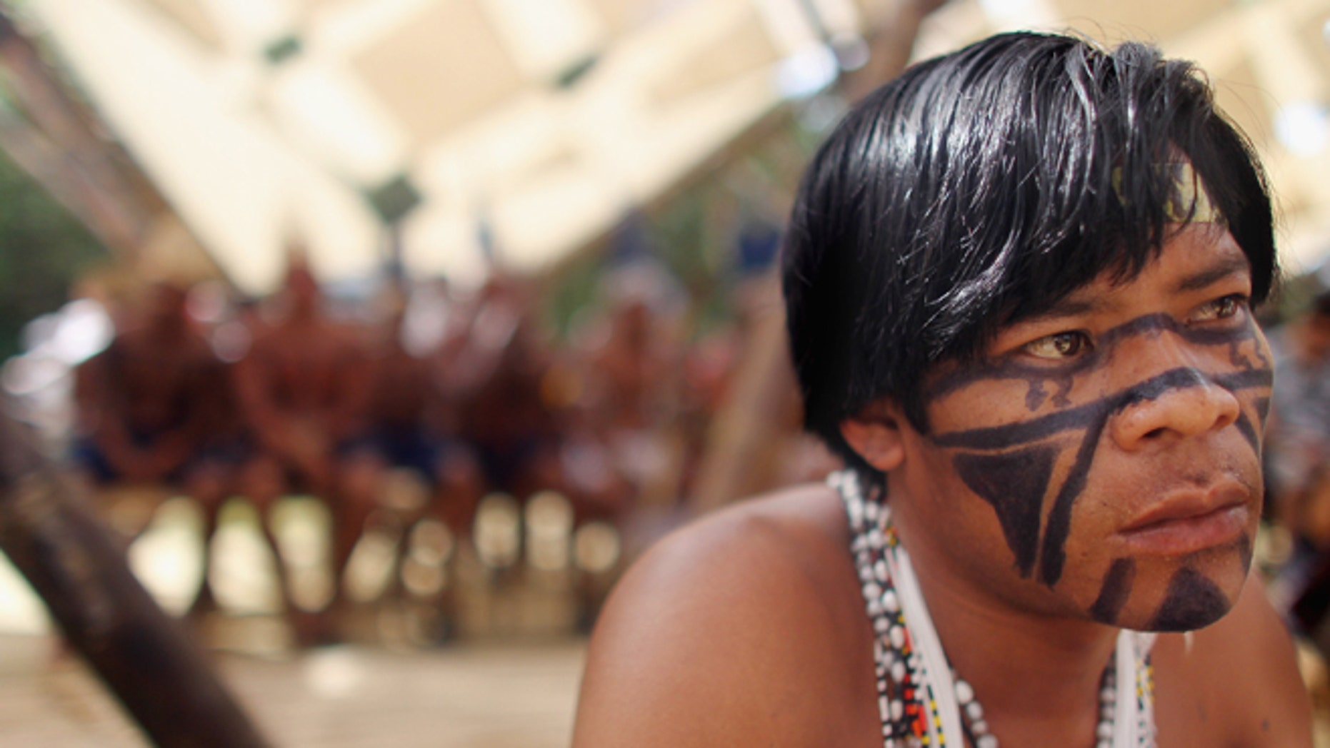 RIO DE JANEIRO, BRAZIL - JUNE 19:  An indigenous man watches a ceremony at the Kari-Oca village constructed by indigenous peoples as a counter point to the Rio + 20 conference on June 19, 2012 in Rio de Janeiro, Brazil. More than 1,000 indigenous peoples are residing at the site through the conference. Indigenous groups oppose Brazil's Amazon forest policies including the controversial Belo Monte dam project. Over 100 heads of state and tens of thousands of participants and protesters will descend on Rio de Janeiro, Brazil, June 20-22 for the high-level portion of the Rio+20 United Nations Conference on Sustainable Development or 'Earth Summit'. Host Brazil is caught up in its own dilemma between accelerated growth and environmental preservation. The Brazilian Amazon, home to 60 percent of the world's largest forest and 20 percent of the Earth's oxygen, remains threatened by the rapid development of the country. The summit aims to overcome years of deadlock over environmental concerns and marks the 20th anniversary of the landmark Earth Summit in Rio in 1992, which delivered the Climate Convention and a host of other promises. Brazil is now the world's sixth largest economy and is set to host the 2014 World Cup and 2016 Summer Olympics.  (Photo by Mario Tama/Getty Images)