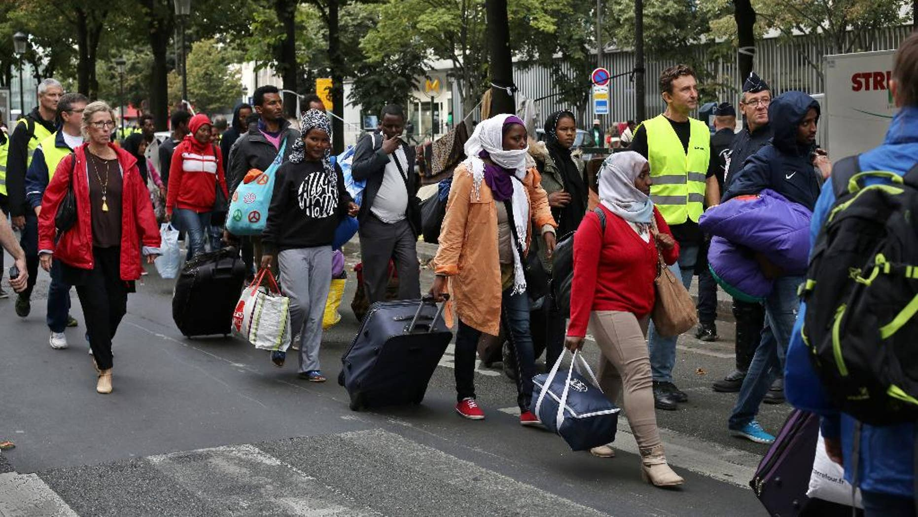 Migrants are evacuated from a camp in the north of Paris, Friday, Sept. 16, 2016. Police and city officials are evacuating hundreds of migrants who had been living on the streets of northern Paris for weeks, in the latest of a string of attempts to find solutions for France's migrants. (AP Photo/Thibault Camus)
