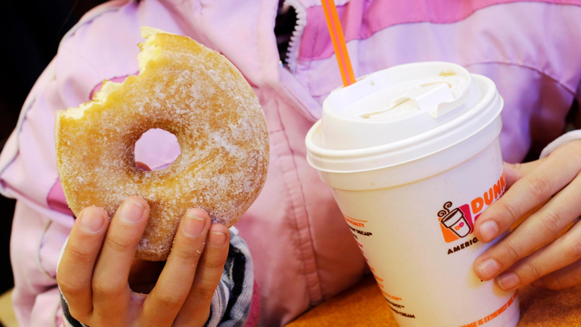FILE - In this Feb. 14, 2013 file photo, a girl holds a beverage, served in a foam cup, and a donut at a Dunkin' Donuts in New York. The New York City Council's sanitation committee has a hearing set for Monday, Nov. 25, 2013, on proposals to ban plastic-foam food containers or explore recycling them. (AP Photo/Mark Lennihan, File)