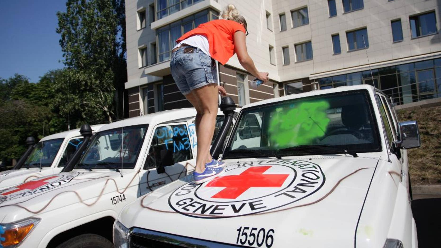 A demonstrator uses spray-paint to deface the windshield of a car of the OSCE and the International Committee of the Red Cross during a protest in Donetsk, eastern Ukraine, Thursday, July  23, 2015. Observers at the Organization for Security and Cooperation and Security in Europe say protesters in rebel-controlled Donetsk vandalized their cars on Thursday showed several dozen protesters outside the hotel where OSCE observers were staying. Some of them, young men wearing sunglasses, spray-painted the cars of the OSCE and the International Committee of the Red Cross in the parking lot.  (AP Photo/Alexander Ermochenko)