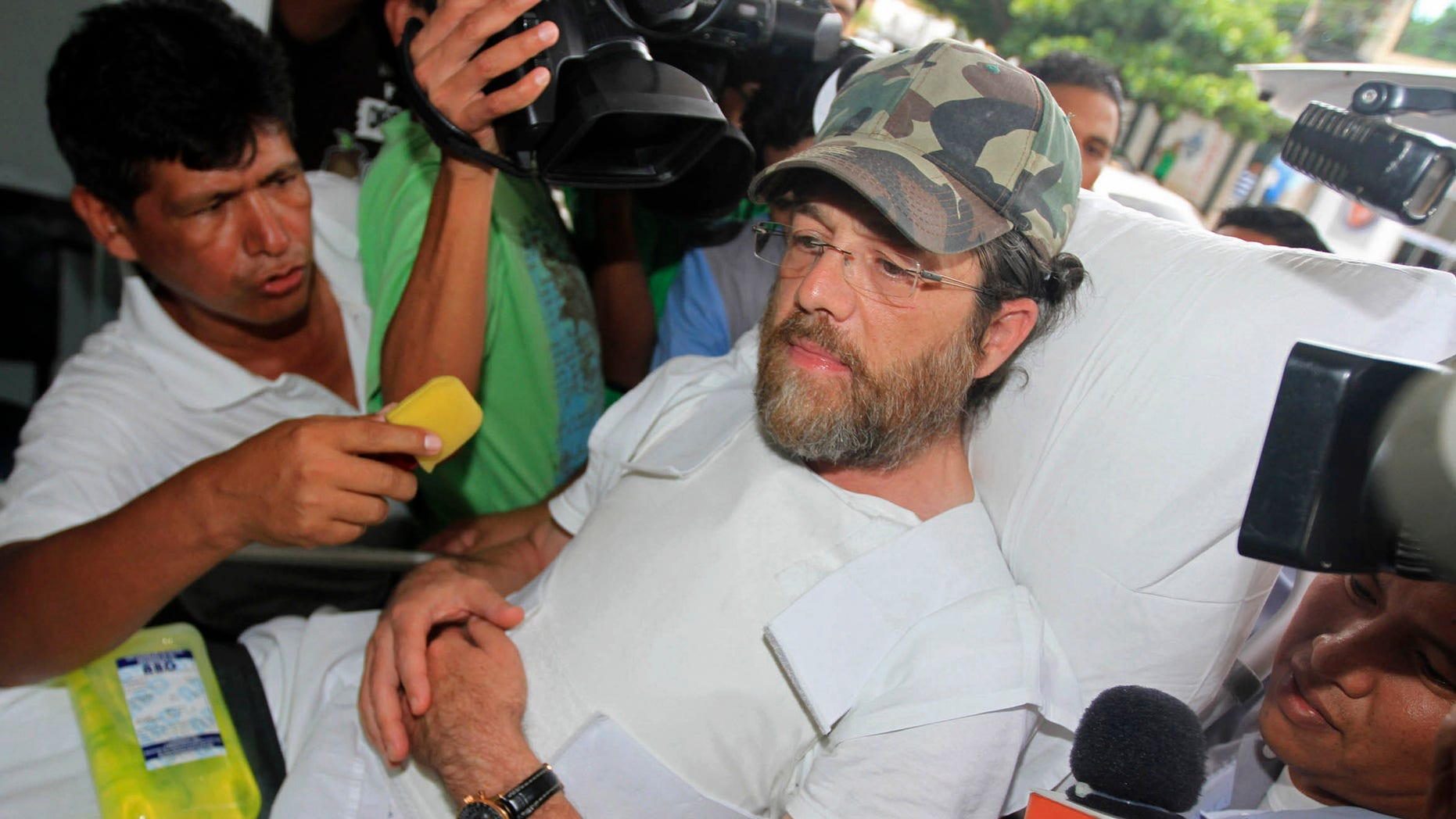 Dec. 11, 2012: Members of the press surround U.S. businessman Jacob Ostreicher as he arrives in a hospital bed wearing a flak jacket to his court hearing in Santa Cruz, Bolivia.