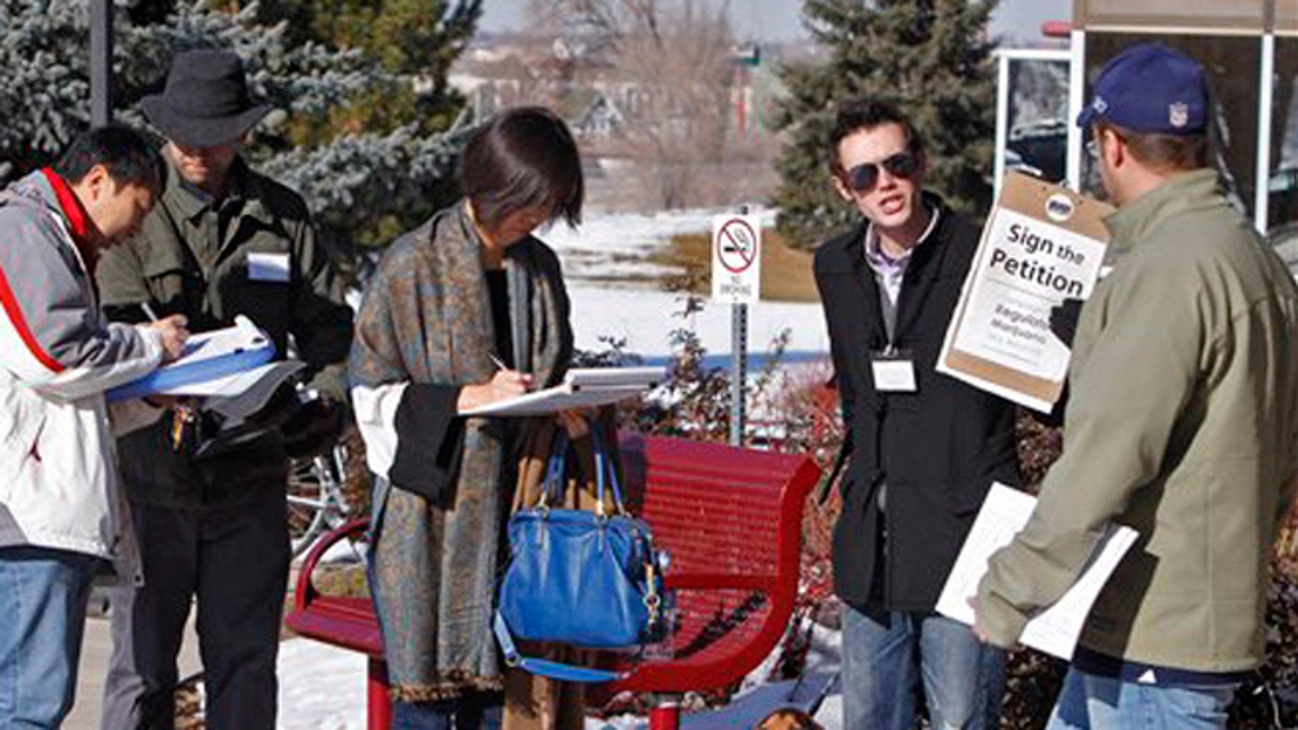 FILE: Dec. 8, 2011: Volunteers  collect signatures on a petition to legalize marijuana in Colorado.