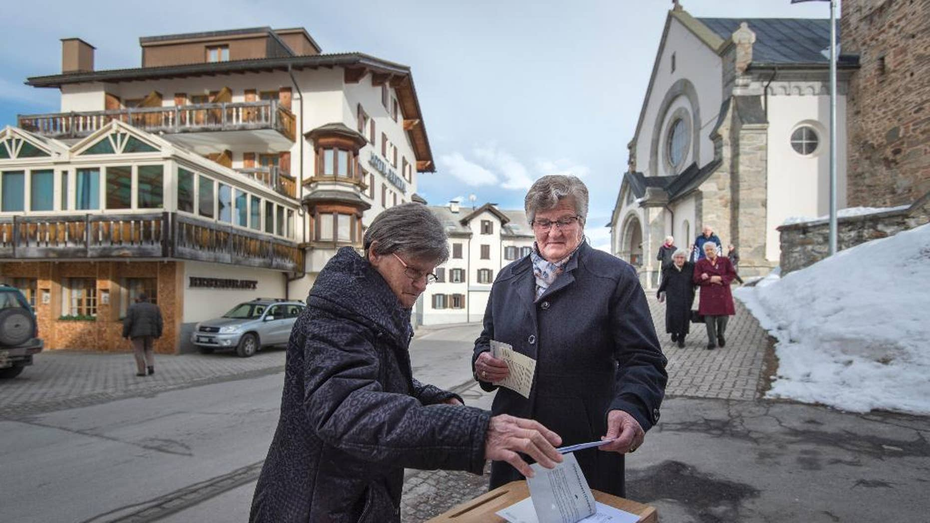 """Swiss voters cast their ballot in Obersaxen, Switzerland, Sunday Feb. 12, 2017. Swiss voters were deciding Sunday whether to make it easier for """"third-generation foreigners"""" to get Swiss citizenship and whether to lock in competitive low tax rates for foreign companies in Switzerland. (Benjamin Manser/Keystone via AP)"""