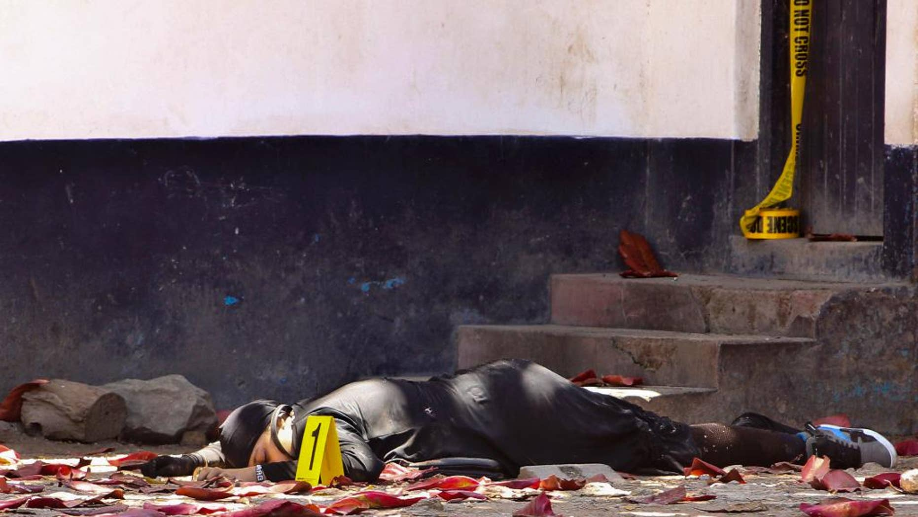 FILE- In this file photo dated Sunday Sept.11, 2016, one of the bodies of three women who were shot dead by police, outside the central police station in the coastal city of Mombasa, Kenya. Human rights activists with the Muslims for Human Rights group, on Friday Sept. 23, 2016, accused Kenyan police of executing three women who allegedly attacked a police station this month after pledging allegiance to the Islamic State group. (AP Photo / FILE)