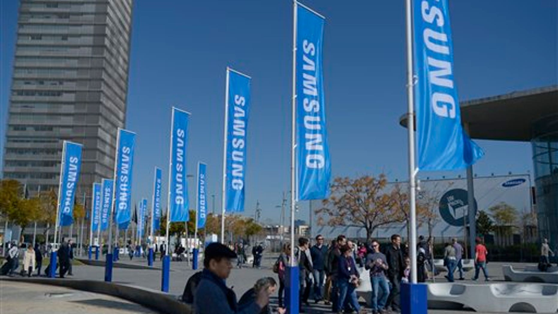 Visitors walk outside  the Mobile World Congress, the world's largest mobile phone trade show, in Barcelona, Spain, Sunday, Feb. 23, 2014. (AP Photo/Manu Fernandez)