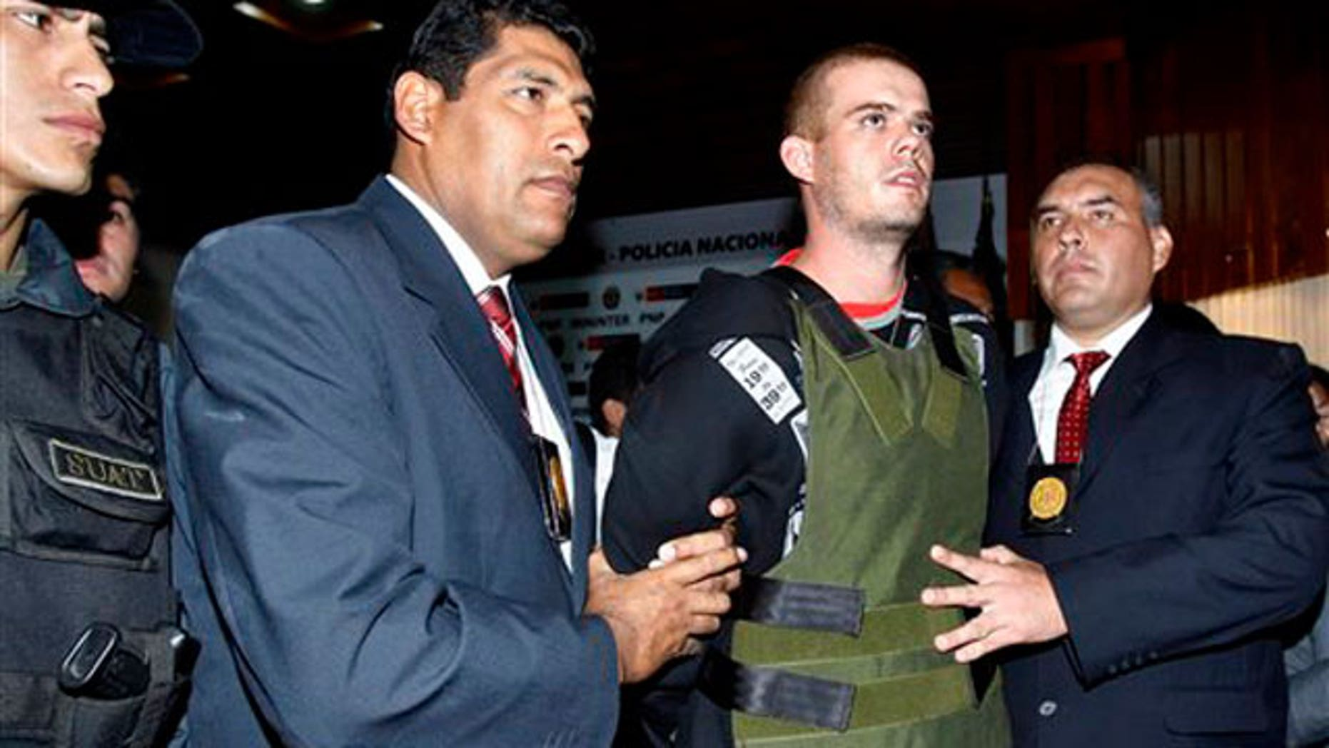 June 5, 2010: Police officers escort Joran van der Sloot, second right, during a press conference at a police station in Lima, Peru.