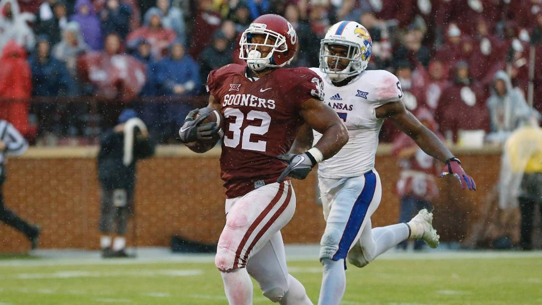 Oklahoma's Samaje Perine (32) runs into the end zone for a touchdown in front of Kansas's Isaiah Johnson (5) in the third quarter of an NCAA college football game in Norman, Okla., Saturday, Nov. 22, 2014. Oklahoma won 44-7. Perine broke the NCAA FBS single-game rushing record of 408 yards, set last week by Wisconsin's Melvin Gordon, with 427 yards. (AP Photo/Sue Ogrocki)