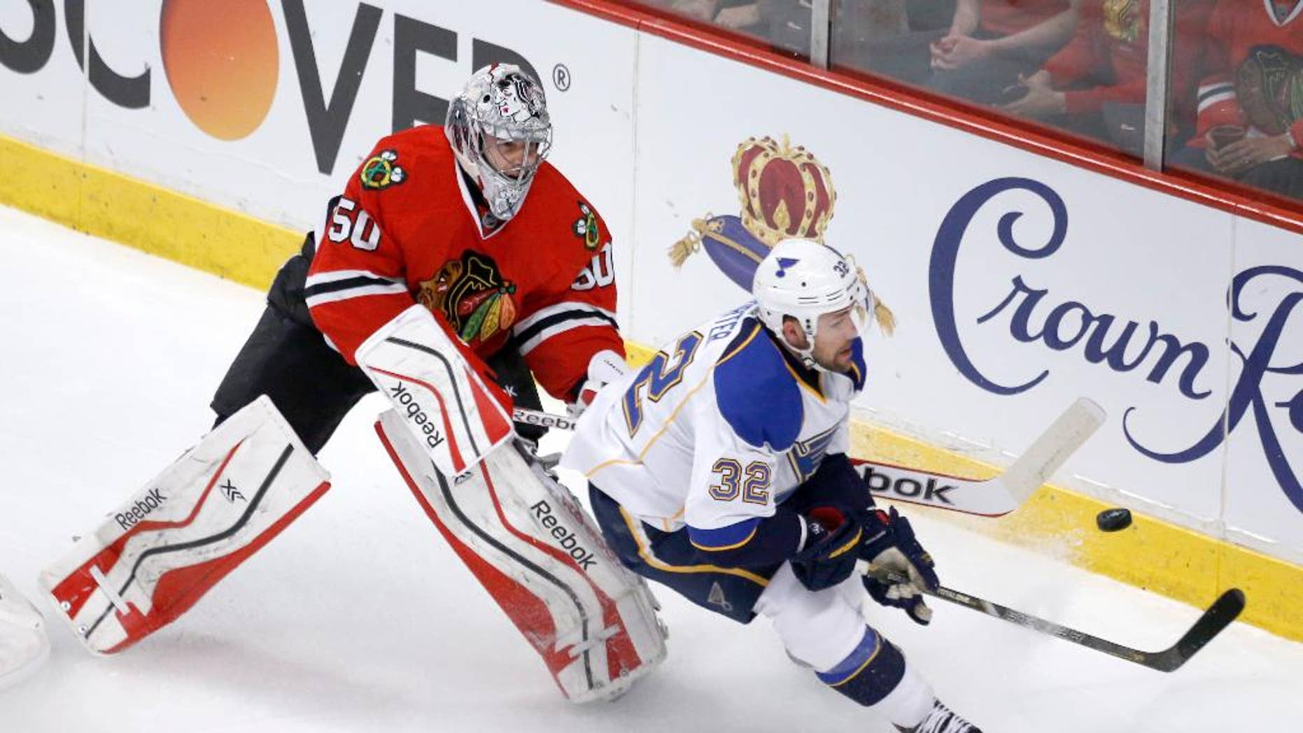 Chicago Blackhawks goalie Corey Crawford (50) clears the puck away from St. Louis Blues left wing Chris Porter during the first period in Game 3 of a first-round NHL hockey Stanley Cup playoff series game Monday, April 21, 2014, in Chicago. (AP Photo/Charles Rex Arbogast)
