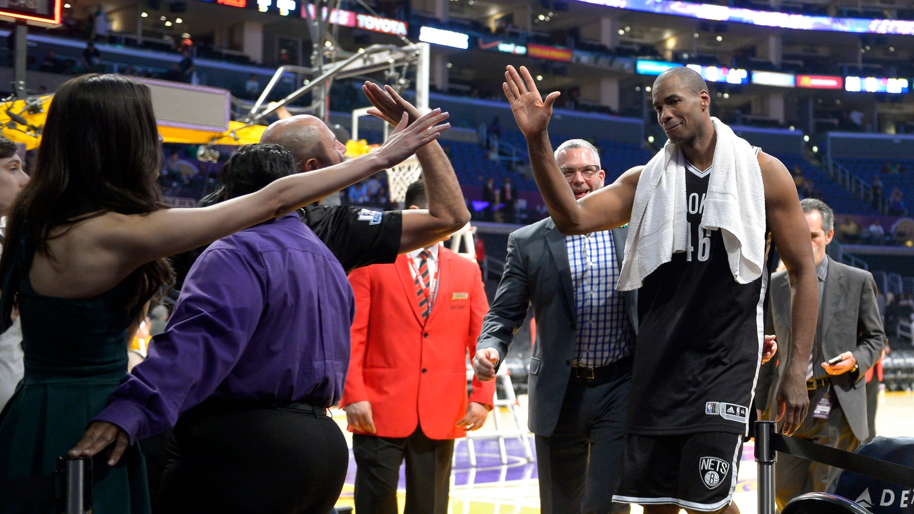 Brooklyn Nets center Jason Collins, right, is congratulated by fans after they defeated the Los Angeles Lakers in an NBA basketball game, Sunday, Feb. 23, 2014, in Los Angeles. Brooklyn won 108-102. (AP Photo/Mark J. Terrill)