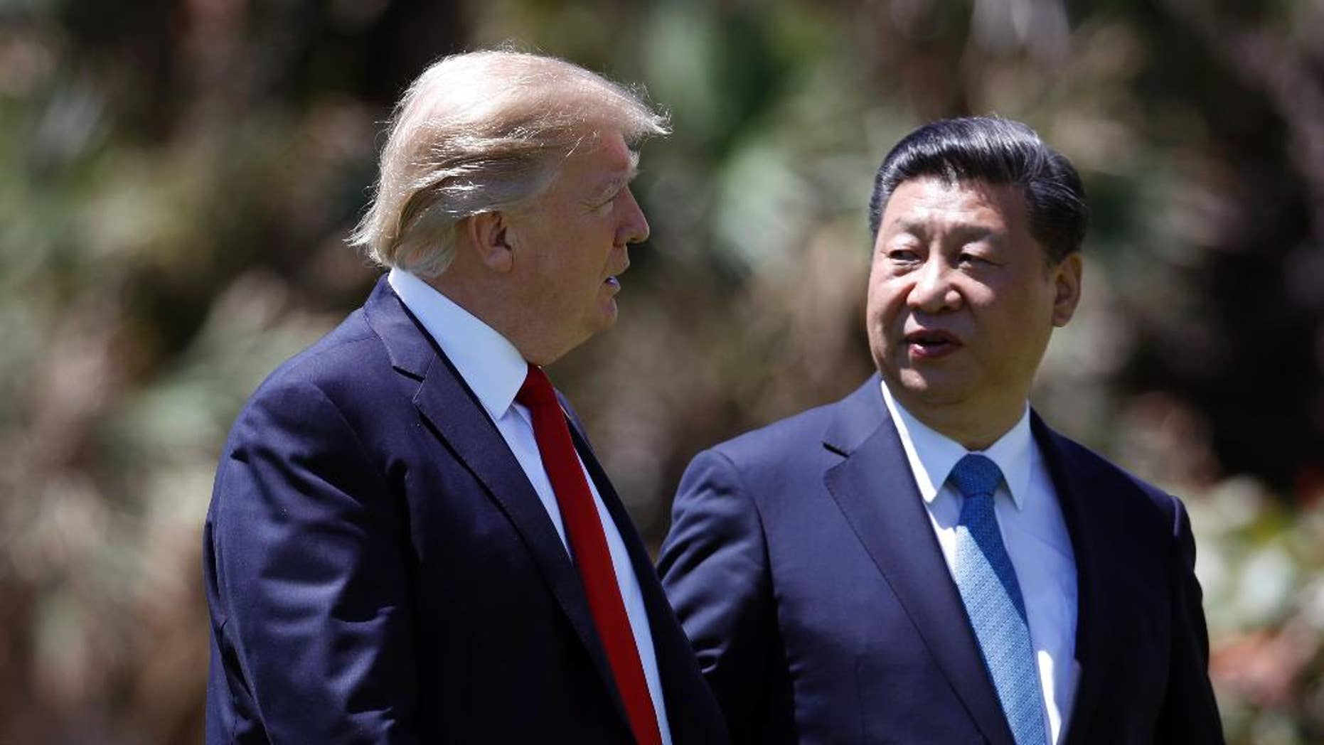 "FILE - In this April 7, 2017 file photo, President Donald Trump, left, and Chinese President Xi Jinping walk together after their meetings at Mar-a-Lago, in Palm Beach, Fla. Trump has praised Xi since hosting him at his Palm Beach, Fla., resort, after sharply criticizing China's economic policies as a candidate. Since taking office, Trump has displayed a striking willingness to embrace autocrats as potential partners in his ""America First"" agenda, even if it means ignoring their heavy-handed tactics and repression at home. (AP Photo/Alex Brandon, File)"
