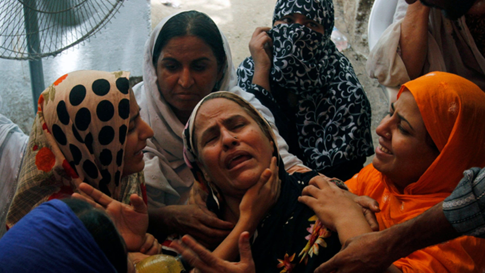 Aug. 19: People comfort a woman who lost her son in Karachi, Pakistan.