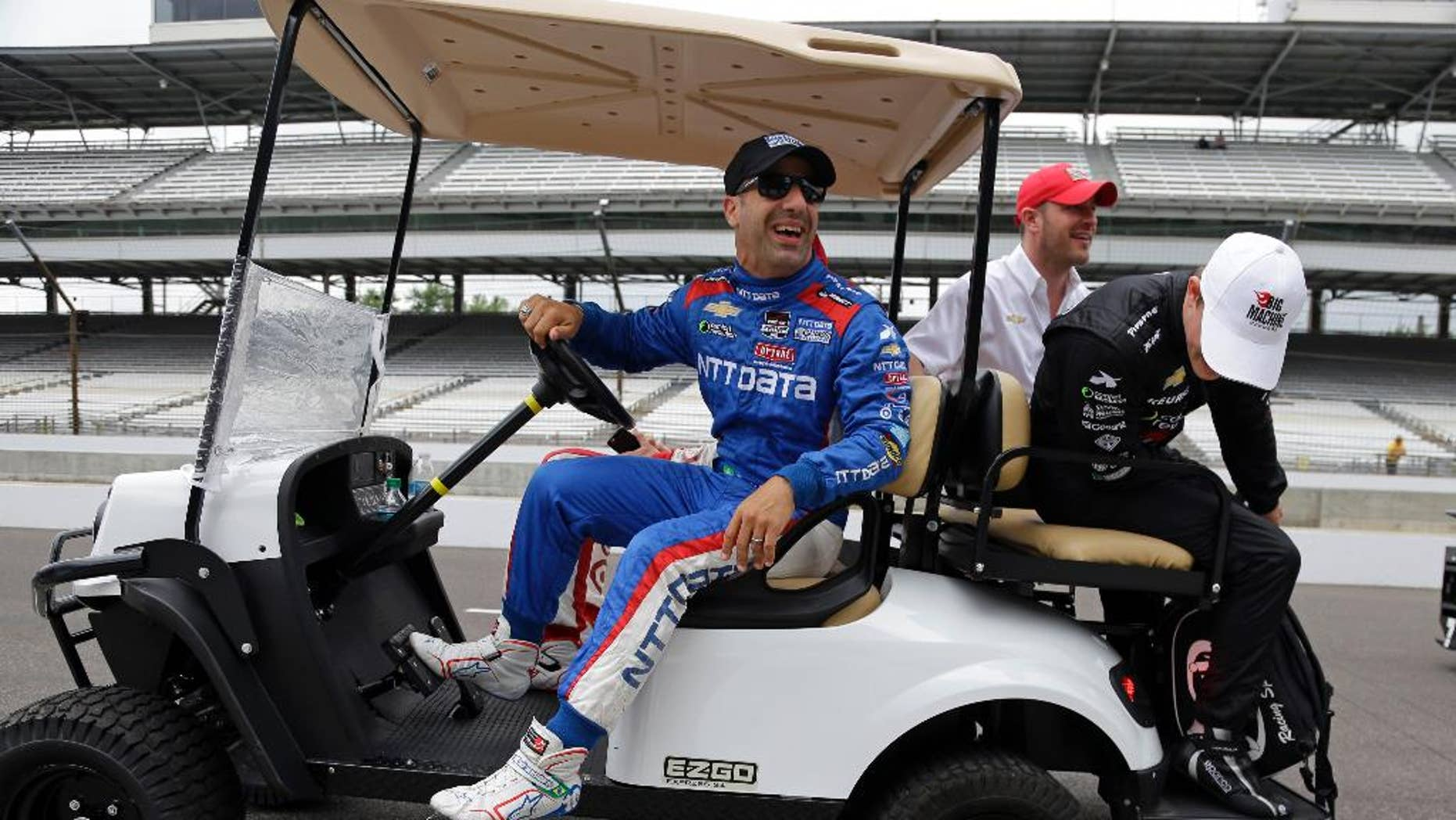 Tony Kanaan, of Brazil, laughs as Sage Karam looks at a flat tire on the cart  they where riding in before the start of practice for the Indianapolis 500 auto race at Indianapolis Motor Speedway in Indianapolis, Monday, May 18, 2015.  (AP Photo/Michael Conroy)