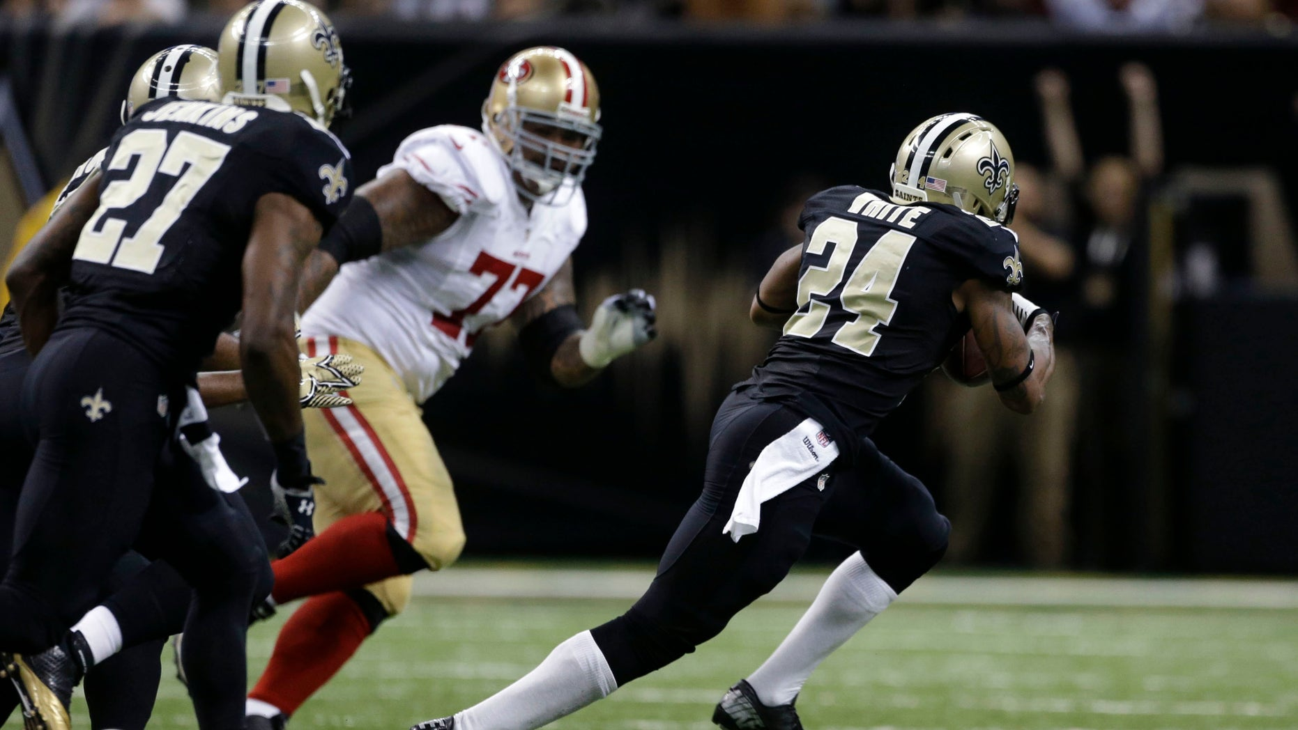 New Orleans Saints cornerback Corey White (24) carries an interception as San Francisco 49ers guard Mike Iupati (77) pursues in the first half of an NFL football game in New Orleans, Sunday, Nov. 17, 2013. (AP Photo/Dave Martin)