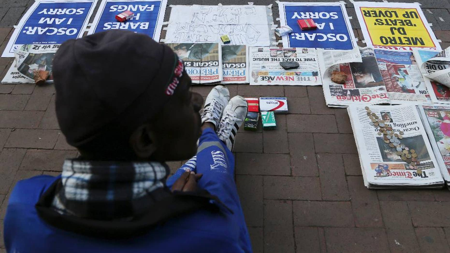 A vendor sells newspaper with headlines on Oscar Pistorius ouside the high court in Pretoria, South Africa, Tuesday, April 8, 2014. Pistorius, who is charged with murder for the shooting death of his girlfriend, Reeva Steenkamp, on Valentines Day in 2013, was testifying for a second day at his murder trial Tuesday, answering questions from his defense lawyer. (AP Photo/Themba Hadebe)