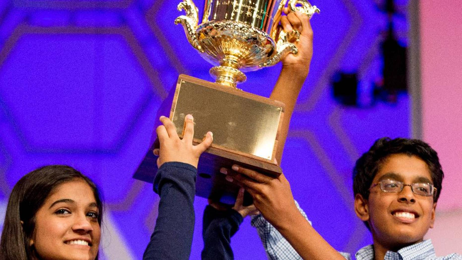 FILE - In this May 28, 2015, file photo, Vanya Shivashankar, 13, left, of Olathe, Kan., left, and Gokul Venkatachalam, 14, of St. Louis, hold up the trophy as co-champions after winning the finals of the Scripps National Spelling Bee in Oxon Hill, Md. The Scripps National Spelling Bee is adding a new wrinkle in 2017 in yet another attempt to stop a streak of ties for the championship. This year, the top spellers will sit for a written tiebreaker test before they begin spelling words in the primetime finale. The results will be revealed only if two or three spellers get through the final rounds unscathed. (AP Photo/Andrew Harnik, File)