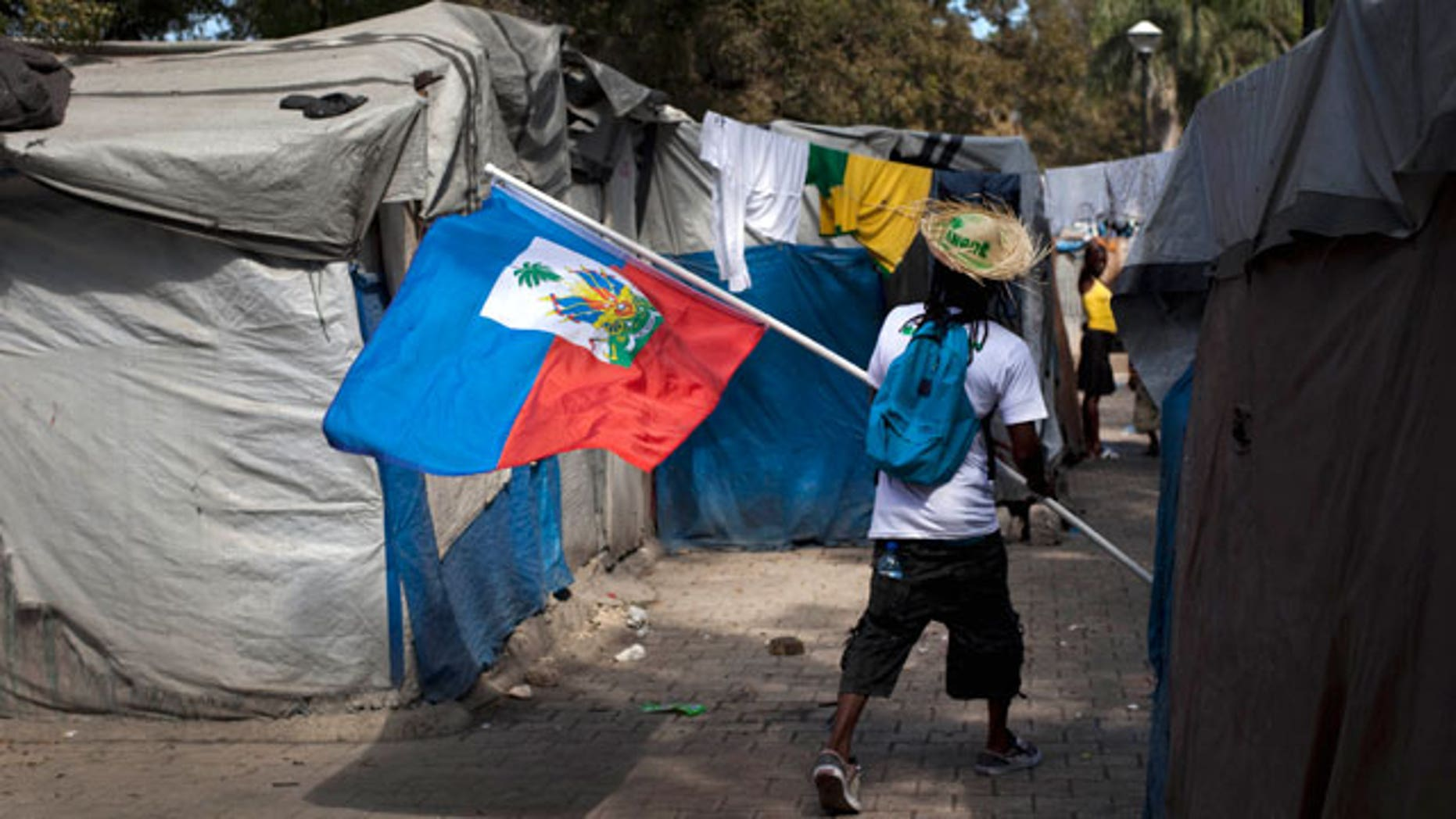 Jan. 11, 2012: A demonstrator carrying a Haitian flag walks through the Champ de Mars camp, across the street from the collapsed National Palace, during a protest to demand new housing, in Port-au-Prince, Haiti.