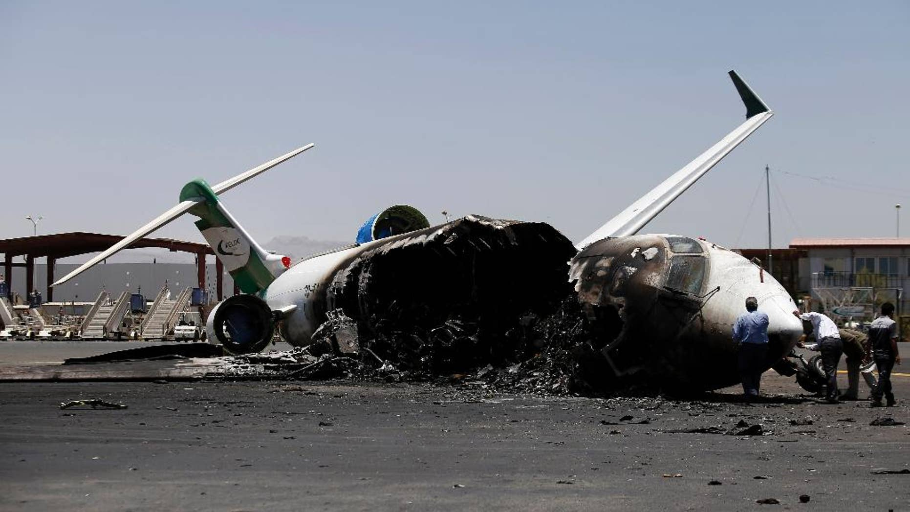 Officials of Felix Airways, a domestic airline, inspect a plane destroyed by Saudi-led airstrikes, at the Sanaa International airport, in Yemen, Wednesday, April 29, 2015. Saudi-led coalition warplanes pounded Shiite rebels and their allies overnight and throughout the day on Tuesday in the Yemeni capital. Around midday, airstrikes hit Sanaa International airport, setting a plane owned by a private company on fire, according to a statement released by the Shiite rebels, known as Houthis. (AP Photo/Hani Mohammed)