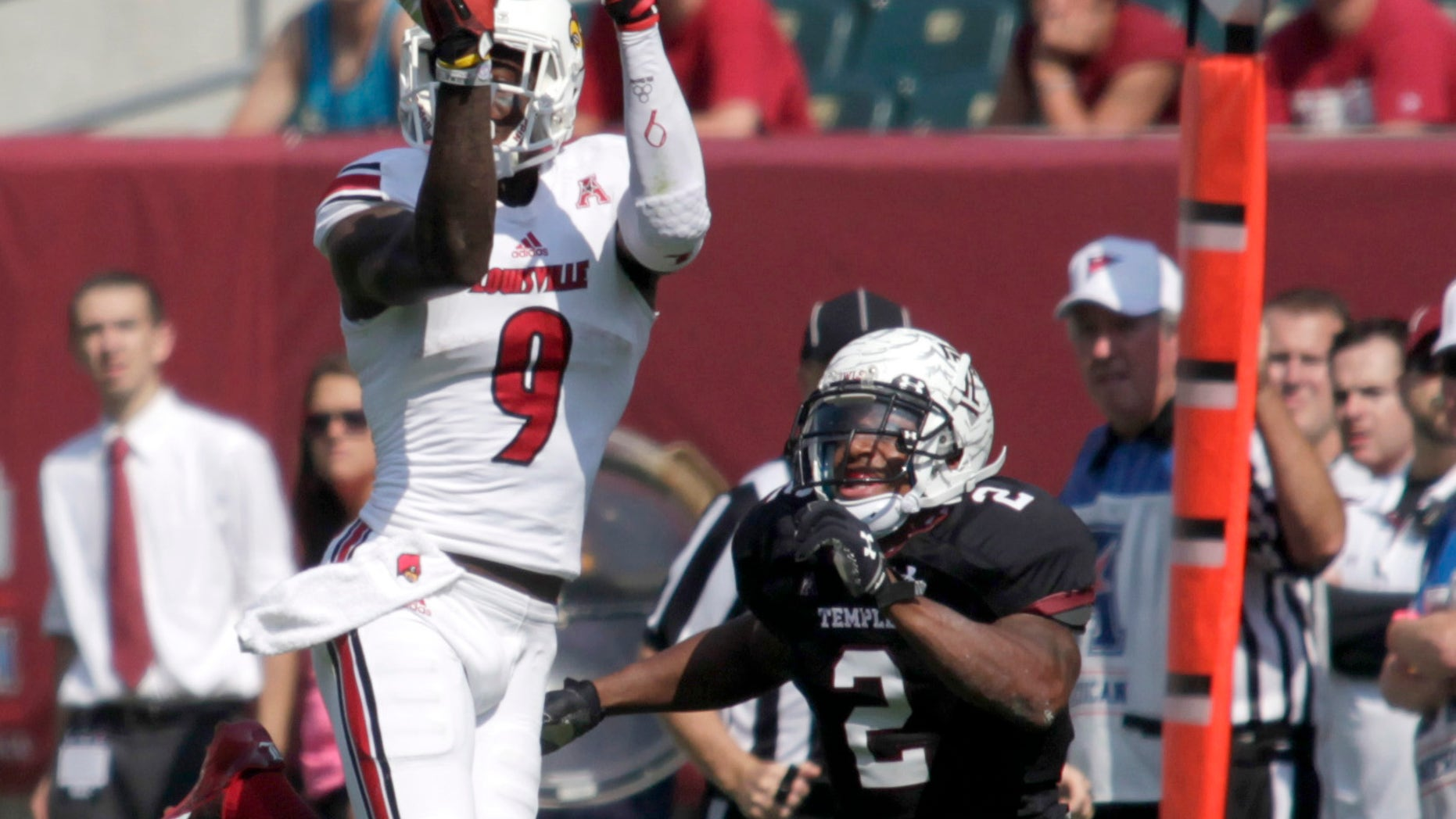 Louisville's  DeVante Parker (9) makes a reception for a first down as Temple's Anthony Robey (2) defends in the first half of an NCAA college football Game, Saturday Oct. 5 , 2013, in Philadelphia.  (AP Photo/H. Rumph Jr)