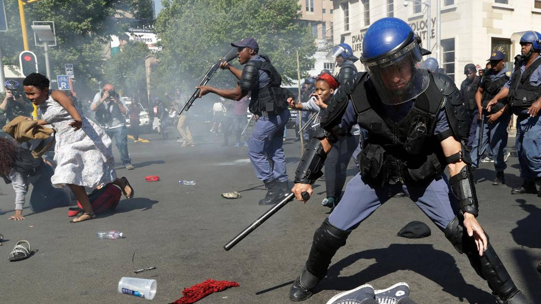 FILE -- In this Wednesday, Sept. 21, 2016 file photo, students run for cover as police fire stun grenades and rubber bullets to disperse them, during a protest for free education at the University of the Witwatersrand in Johannesburg, South Africa. The government on Tuesday, Sept. 27, 2016  called for an investigation, saying protesters were responsible for the death last week at the University of the Witwatersrand in Johannesburg, which has suspended classes because of demonstrations for free education. (AP Photo/Themba Hadebe, File)