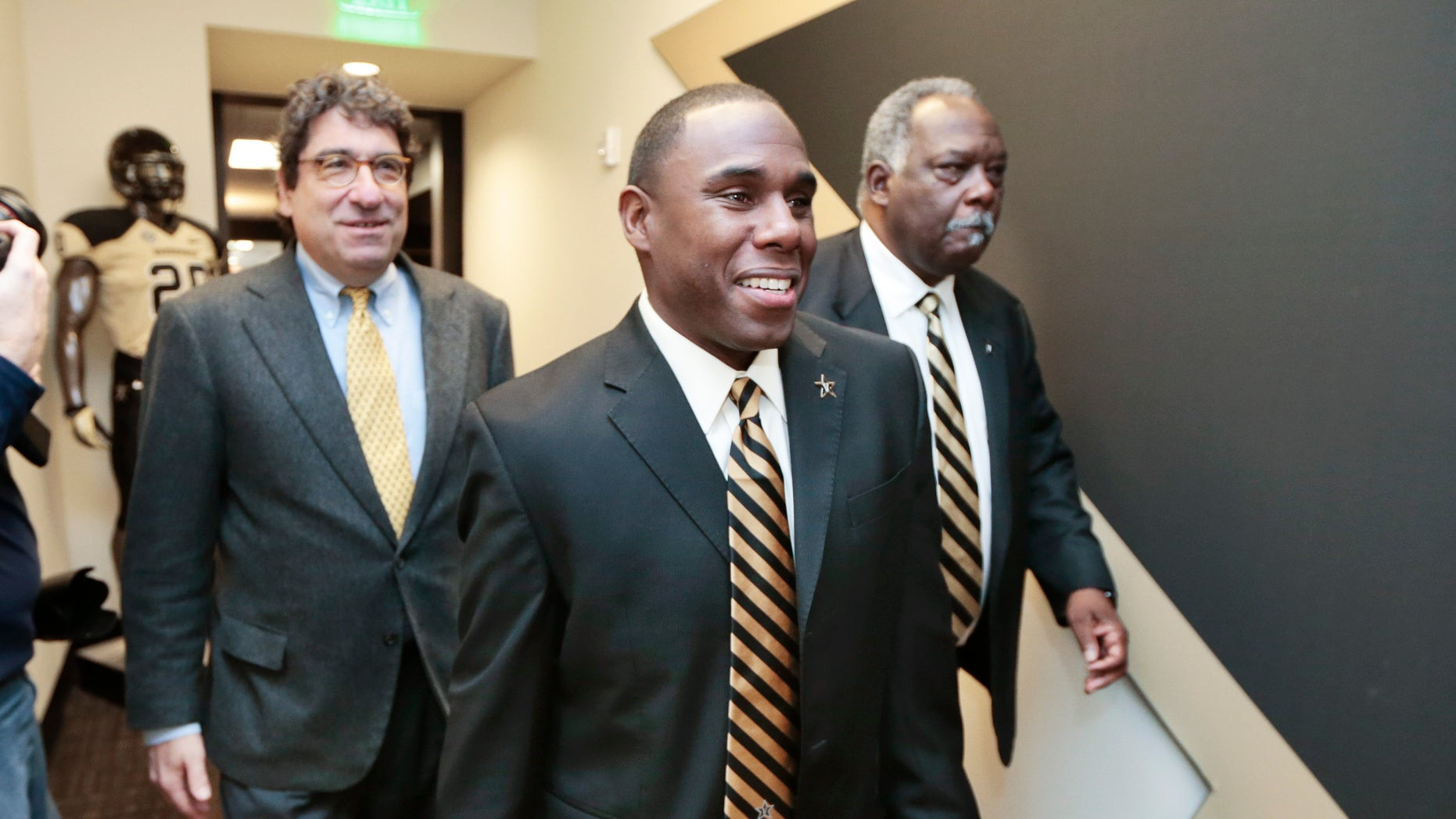 Derek Mason, center, walks to a news conference with Chancellor Nicholas S. Zeppos, left, and athletic director David Williams, right, where Mason is to be introduced as the new Vanderbilt football coach Saturday, Jan. 18, 2014, in Nashville, Tenn. Mason was previously the defensive coordinator at Stanford. (AP Photo/Mark Humphrey)