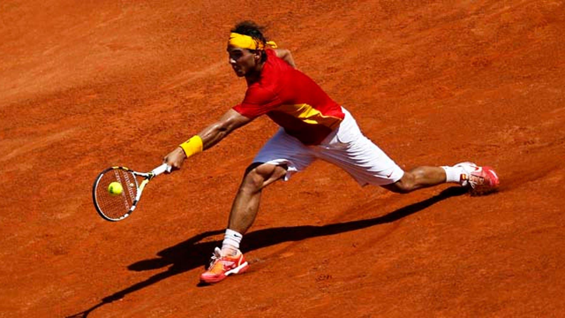Spain's Rafael Nadal plays a shot during a Davis Cup semi-final tennis match against France's Richard Gasquet in the bullring in Cordoba, Spain, Friday, Sep. 16, 2011. (AP Photo/Sergio Torres)