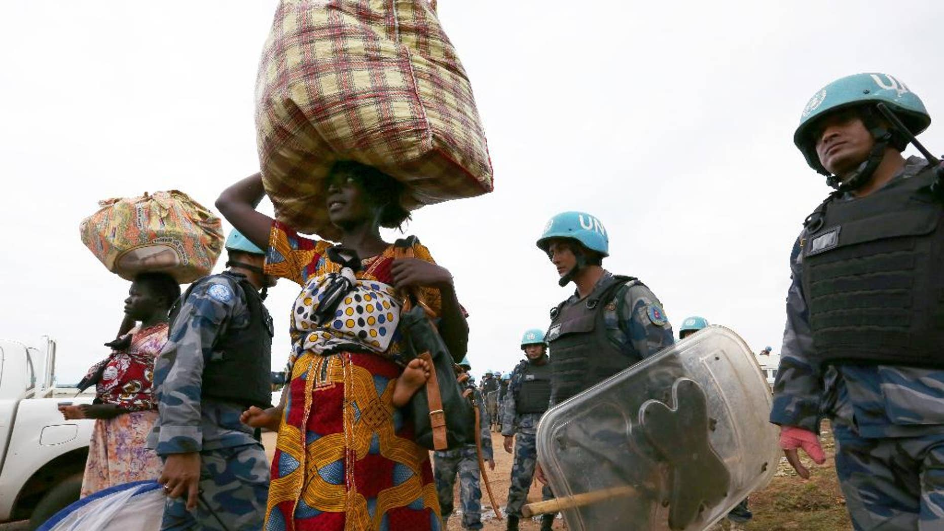 In this photo taken Wednesday, July 13, 2016 and released by the United Nations Mission in South Sudan (UNMISS), villagers and internal displaced people are helped by UN soldiers in the capital Juba, South Sudan. The death toll from a recent outbreak of fighting in South Sudan is almost certain to climb above the 272 people, including 33 civilians, reported by the government, United Nations officials said Wednesday (Eric Kanalstein/UNMISS via AP)