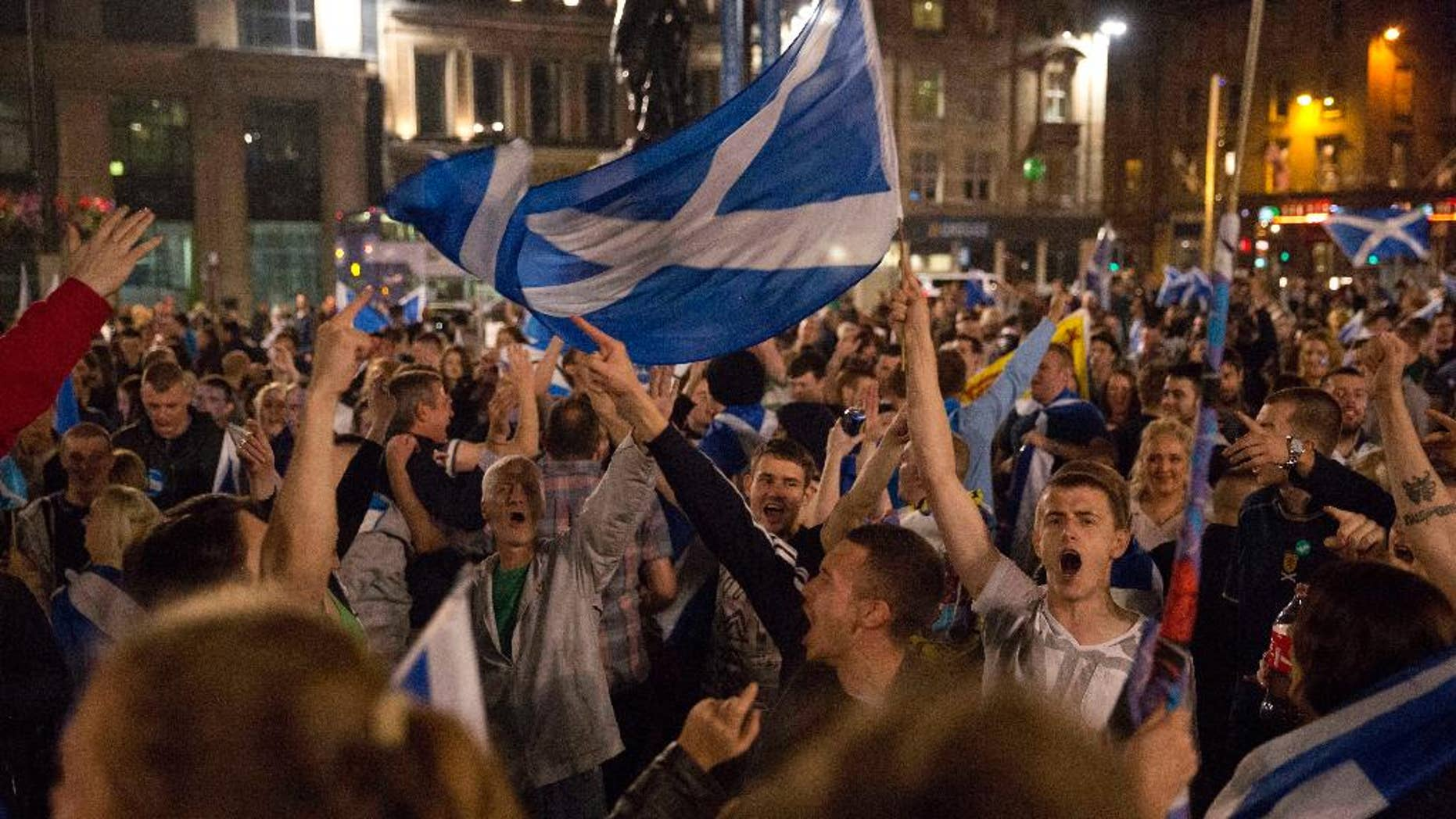 FILE - In this Thursday, Sept. 18, 2014 file photo, supporters of the Yes campaign in the Scottish independence referendum cheer with Scottish Saltire flags as they await the result after the polls closed, in George Square, Glasgow, Scotland. Why Vote Again? Scottish voters decided in a 2014 referendum that they wanted to keep their ties to the U.K. rather than become an independent country. The vote wasn't particularly close, and it's not clear if sentiments have changed since then. (AP Photo/Matt Dunham, File)