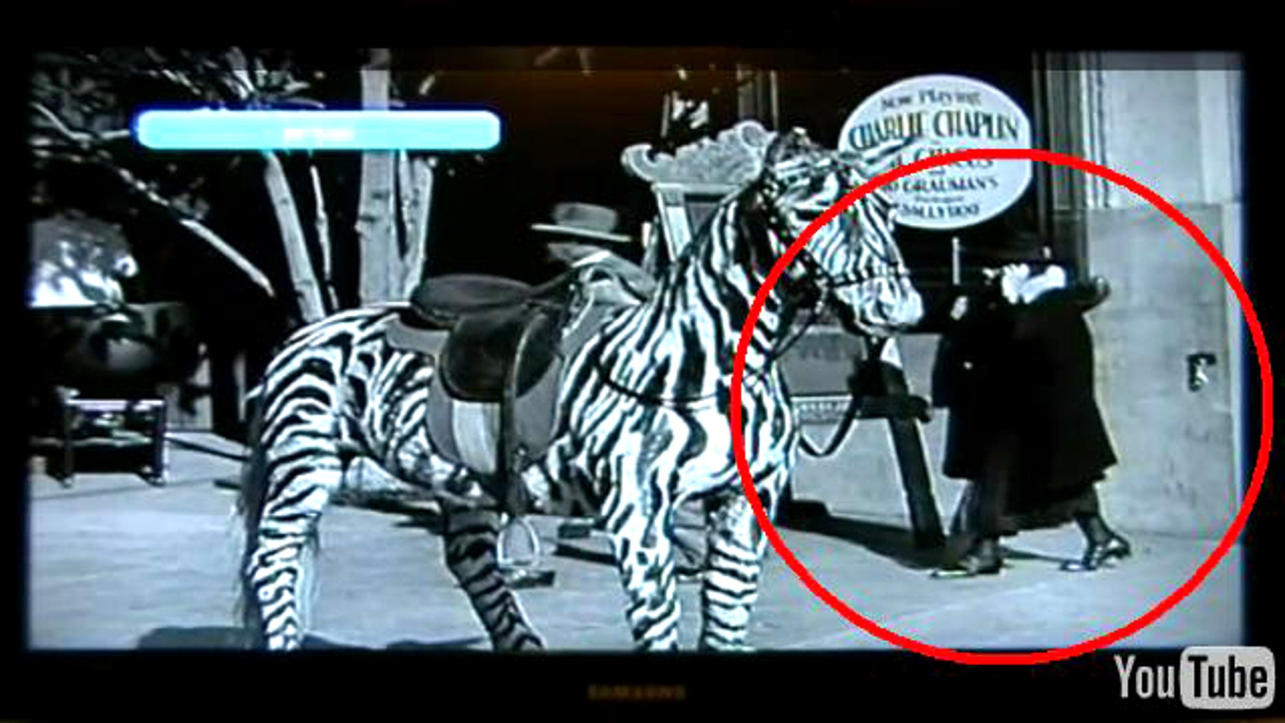 A documentary filmmaker has found an out of place scene in documentary footage released with a Charlie Chaplin movie. The scene shows a large woman dressed in black with a hat hiding most of her face, with what can he describes as a mobile phone, talking as she walks alone.