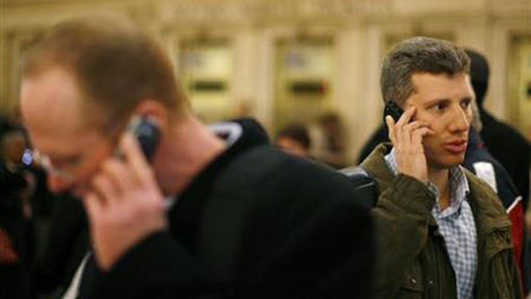 Two men talk on cell phones inside Grand Central Station in New York in this March 4, 2008, file photo. (Reuters Photo)