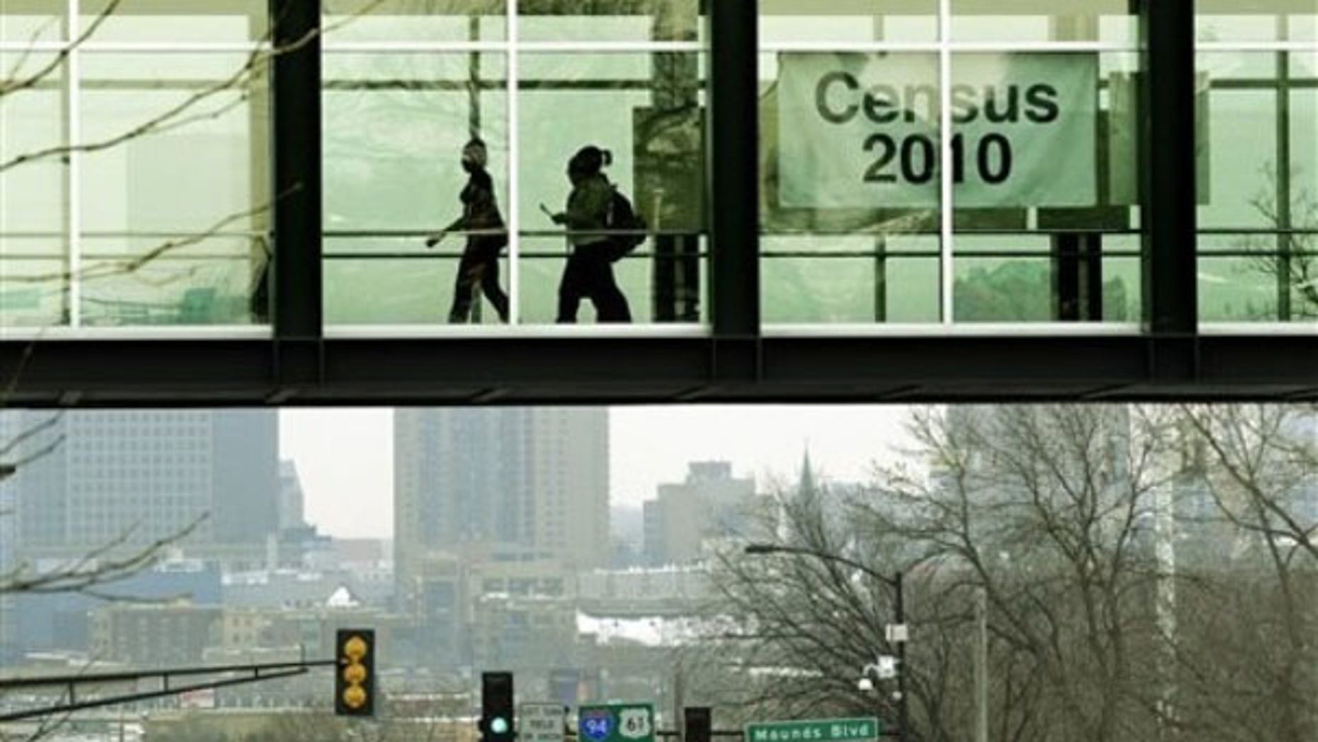 In this Jan. 15, 2010, photo, students at Metropolitan State University in St. Paul, Minn., walk past a census poster. (AP Photo)